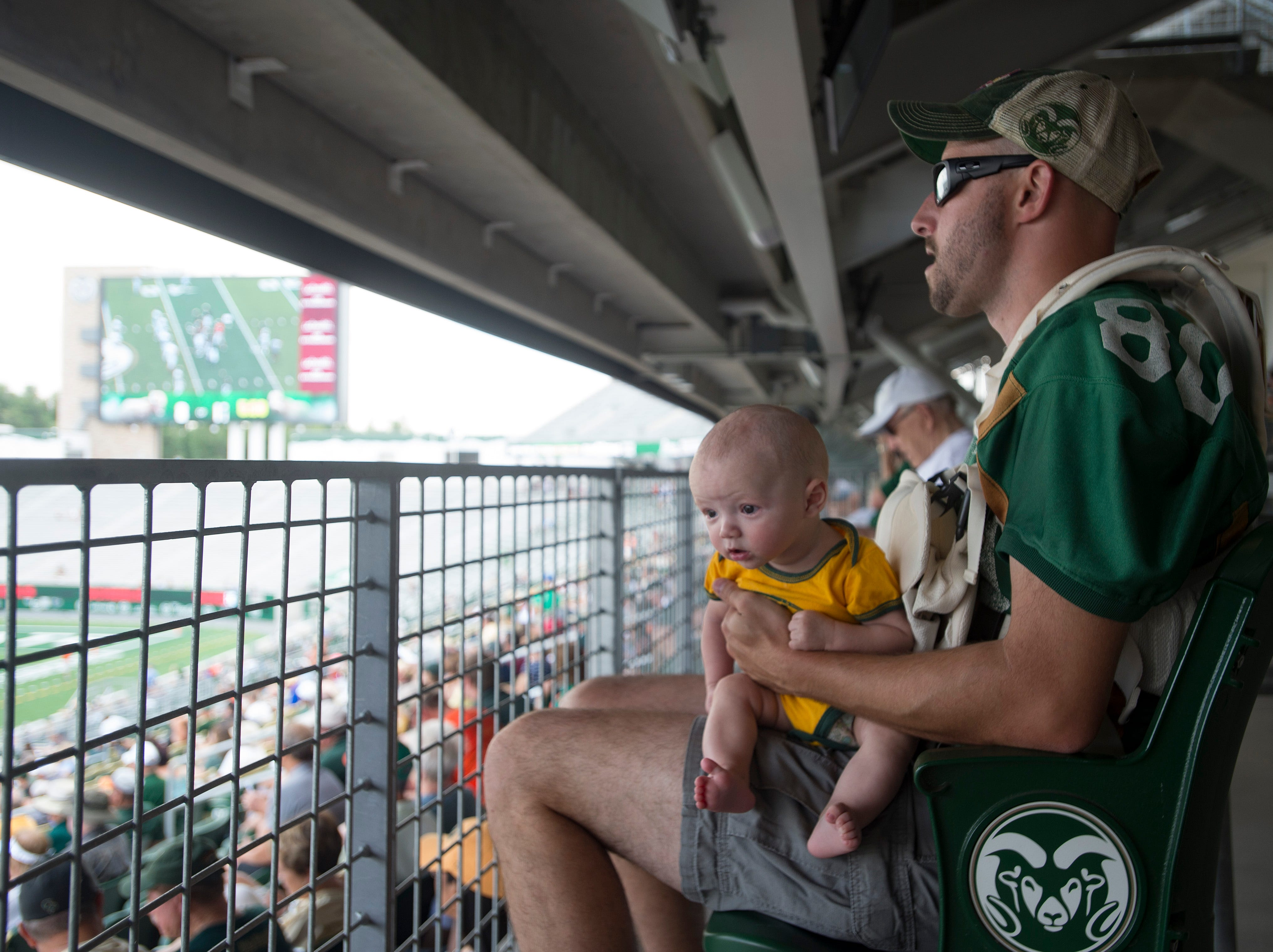 Tyler Shannon watches the Rams scrimmage with his 3-month-old son, Colin, during an open house hosted by the Rams at Canvas Stadium on Saturday, August 4, 2018.