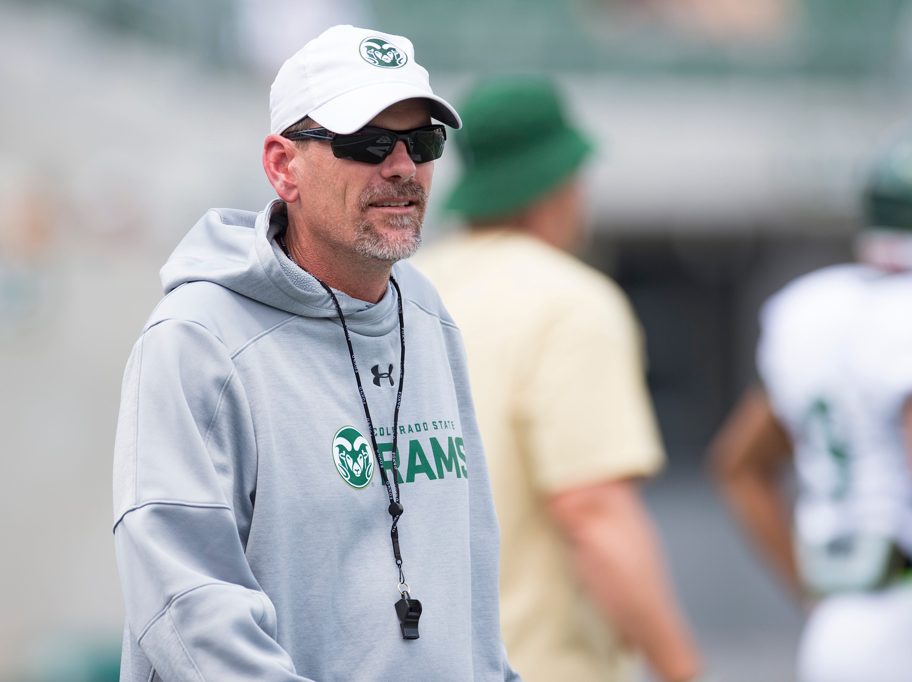 CSU head football coach Mike Bobo watches the Rams warm up for a scrimmage during an open house hosted by the Rams outside of Canvas Stadium on Saturday, August 4, 2018.