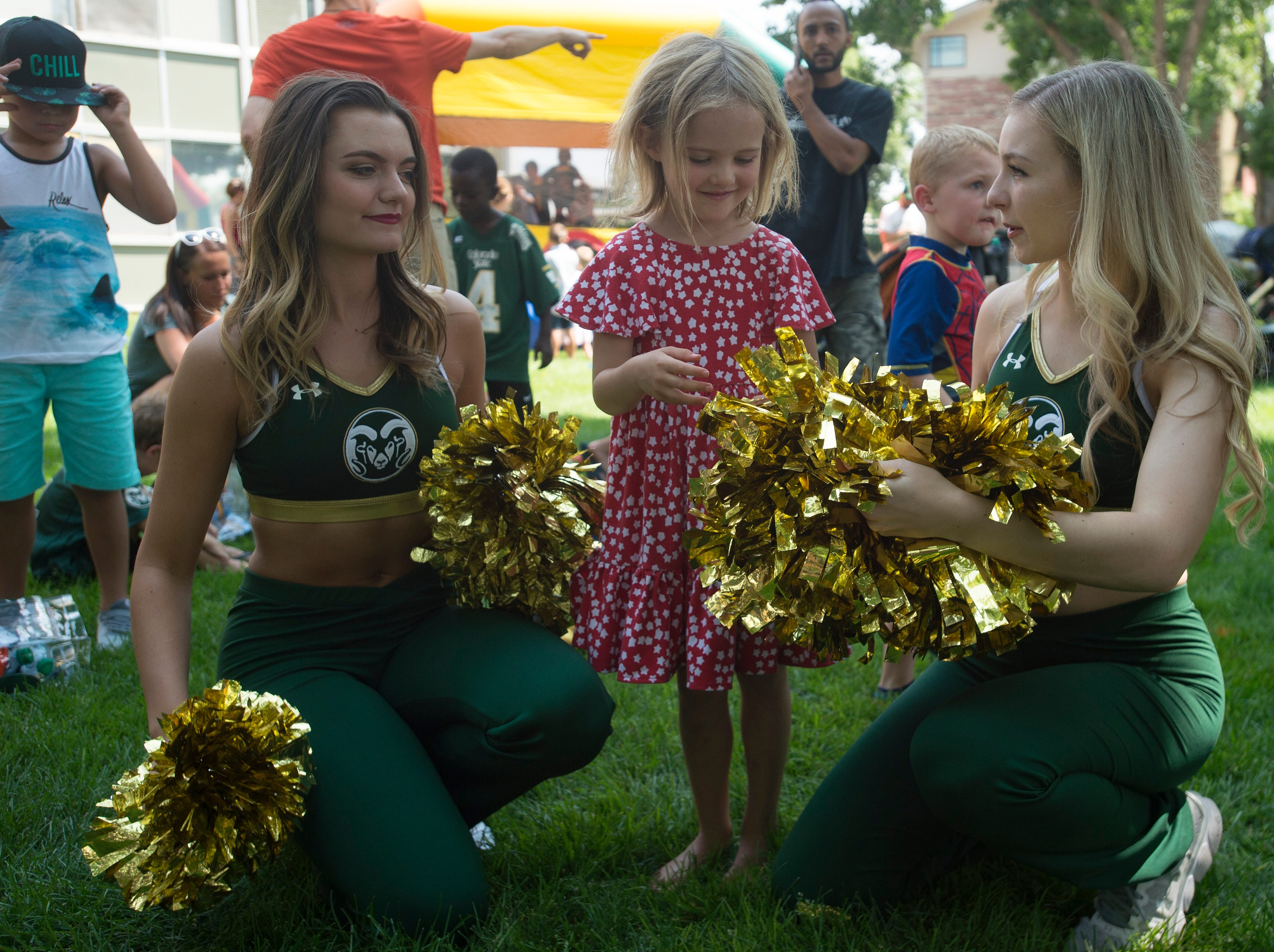Lila Quinn, 5, meets CSU cheerleaders during an open house and scrimmage hosted by the Rams outside of Canvas Stadium on Saturday, August 4, 2018.
