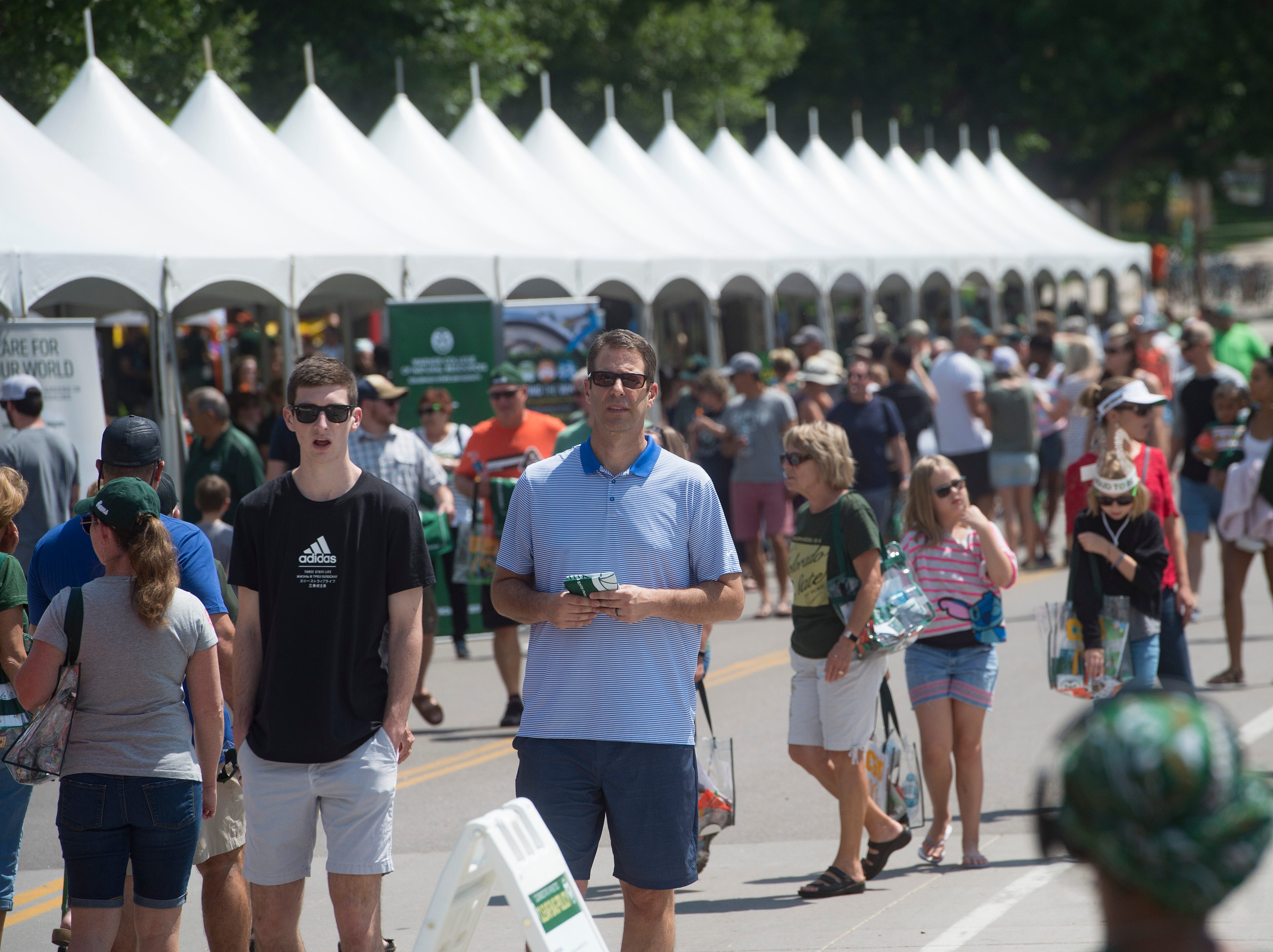 CSU fans visit vendors and booths during an open house and scrimmage hosted by the Rams outside of Canvas Stadium on Saturday, August 4, 2018.