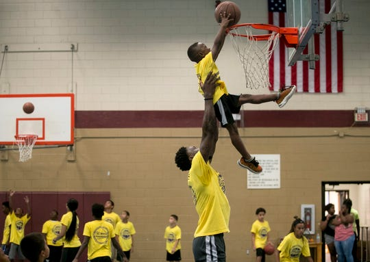 Emmitt Williams lifts Messiah Davis, 5, up so he could dunk a baskeball during the VL Sports Foundation free youth basketball camp at the STARS Complex in Fort Myers on Saturday, August 4, 2018, in Fort Myers.