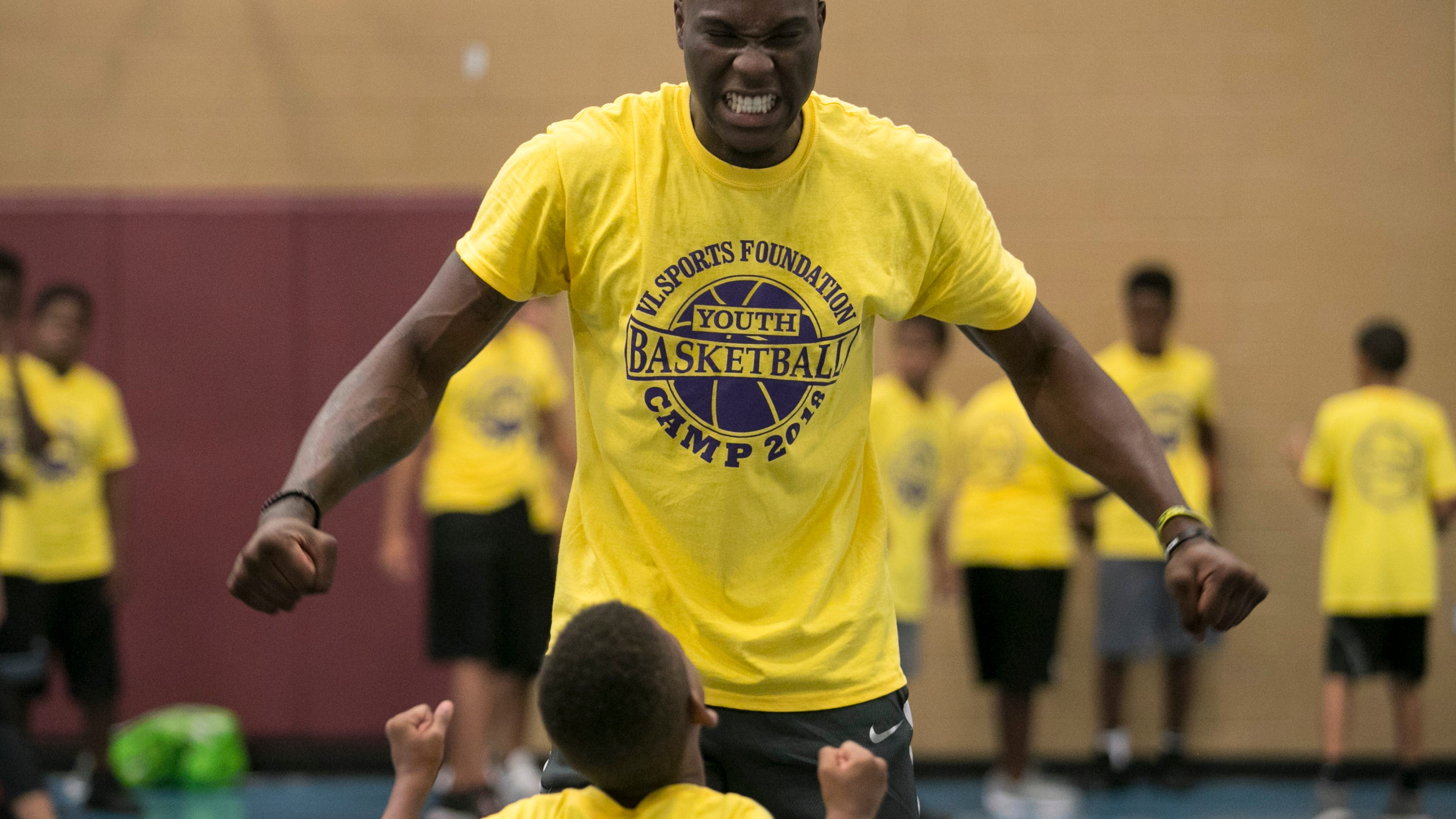 Emmitt Williams gets Chance Hixon, 6, fired up before lifting him for a dunk at the VL Sports Foundation free youth basketball camp Saturday at the STARS Complex in Fort Myers.