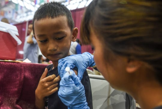 Six-year-old Zayshawn Aguon of Yigo calmly watches as Seventh-day Adventist Guam Clinic nurse volunteer, Leslie Sanga, administers a shot into his arm during the Department of Public Health and Social Services' Back to School Immunization Clinic outreach event at the Micronesia Mall in Dededo on Saturday, Aug. 4, 2018.