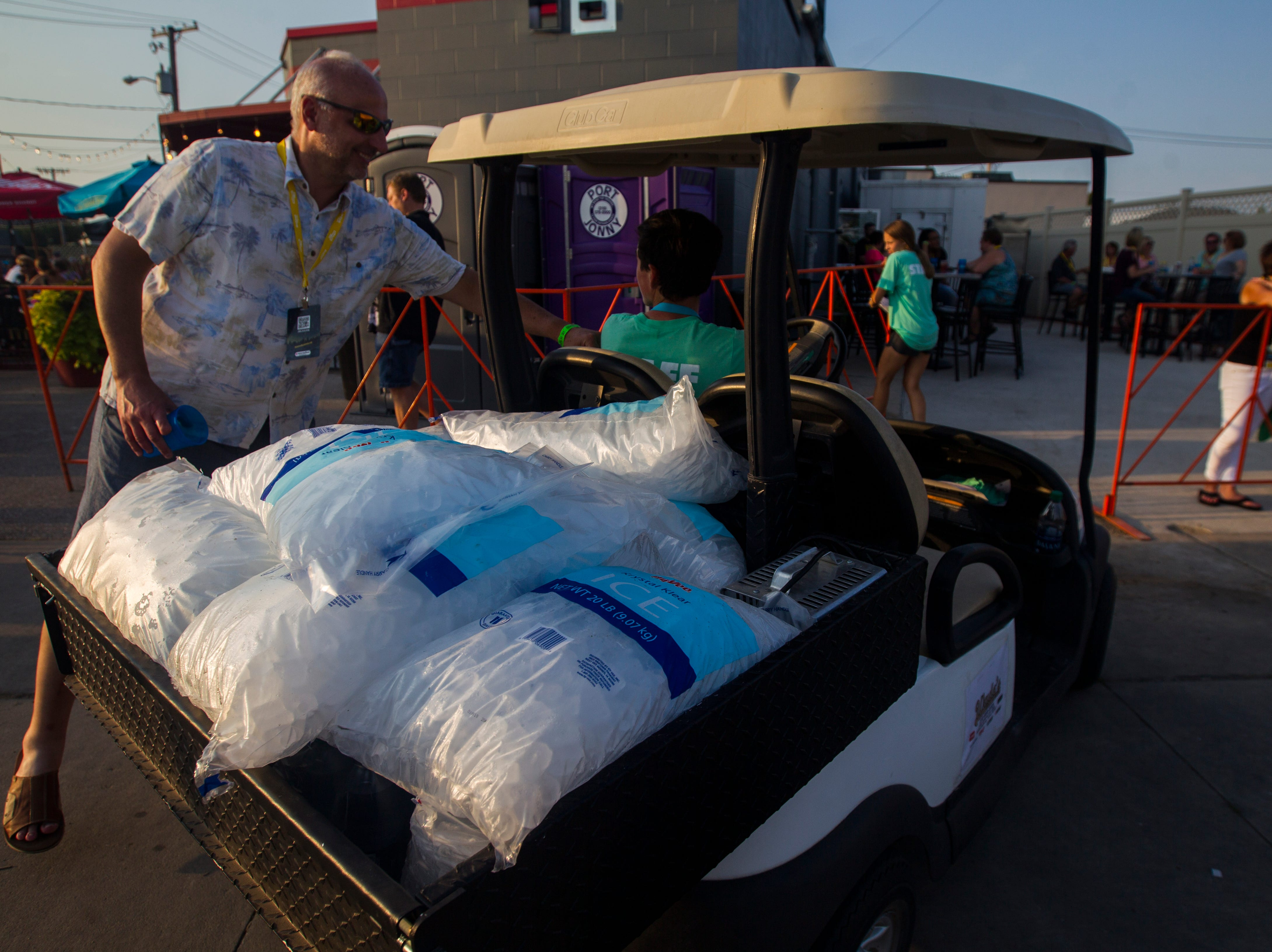 "A cart carrying ice makes its way through a crowd during ""Newbo Evolve"" on Friday, Aug. 3, 2018, in Cedar Rapids, Iowa."