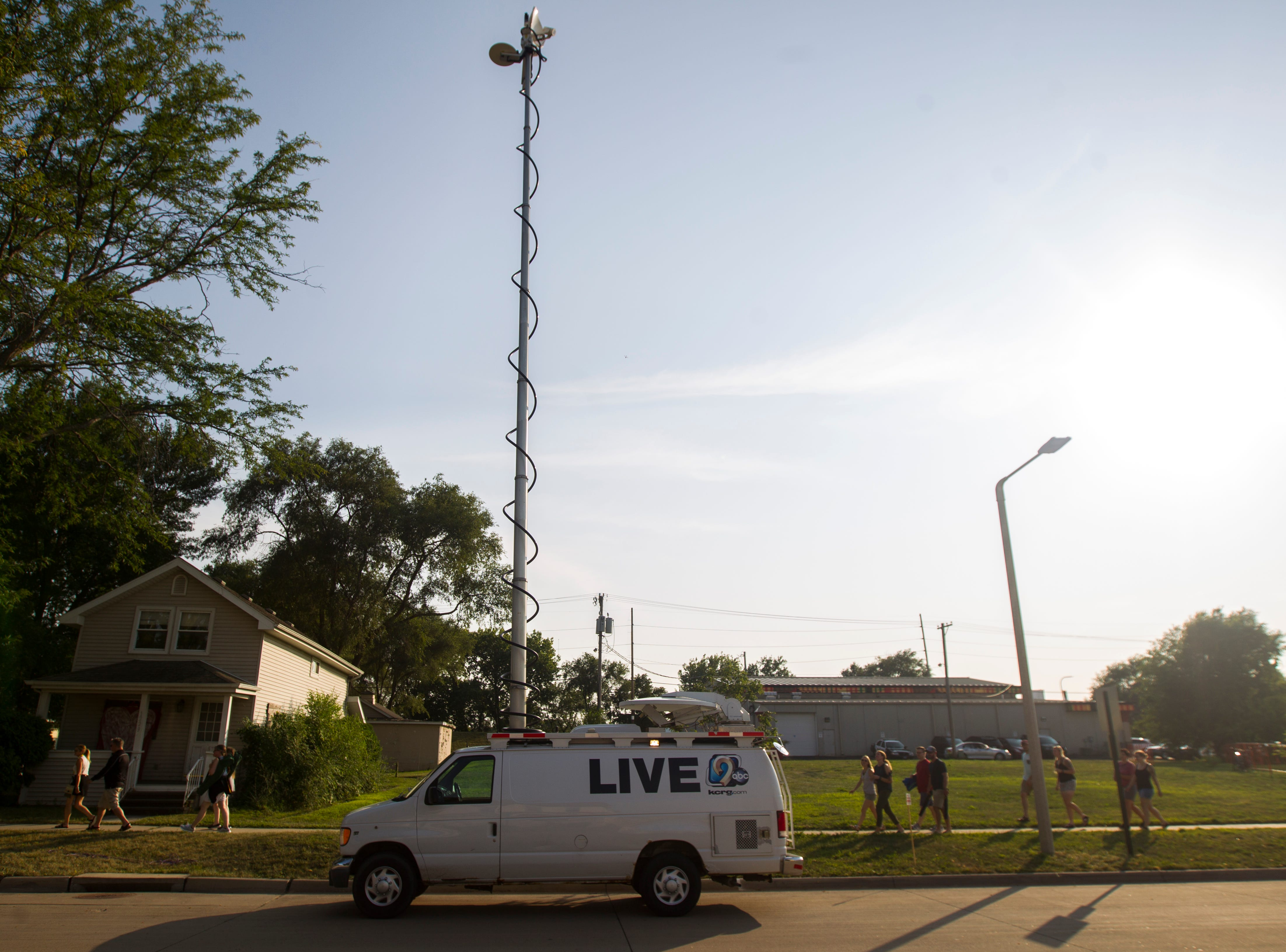 "Concert-goers make their way past a KCRG-TV live truck during ""Newbo Evolve"" on Friday, Aug. 3, 2018, in Cedar Rapids, Iowa."