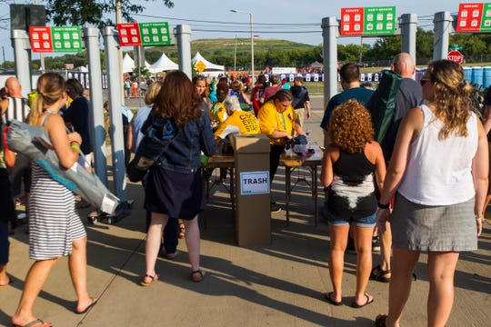 "Concert-goers make their way through security during ""Newbo Evolve"" on Friday, Aug. 3, 2018, in Cedar Rapids, Iowa."