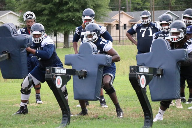 Jackson State players hit the blocking sled during the first day of football practice.