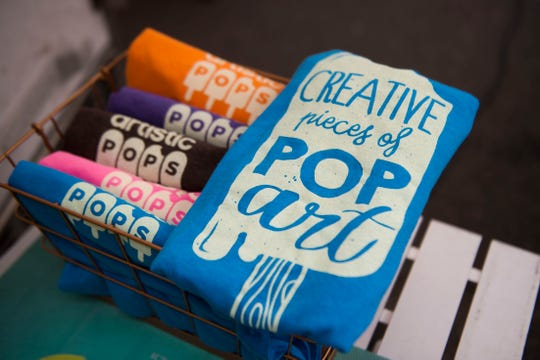 Shirts are available for sale at the Artistic Pops booth at the farmers market in downtown Knoxville on Saturday, Aug. 4, 2018. Artistic Pops are gluten-free, nut-free and dairy-free popsicles.