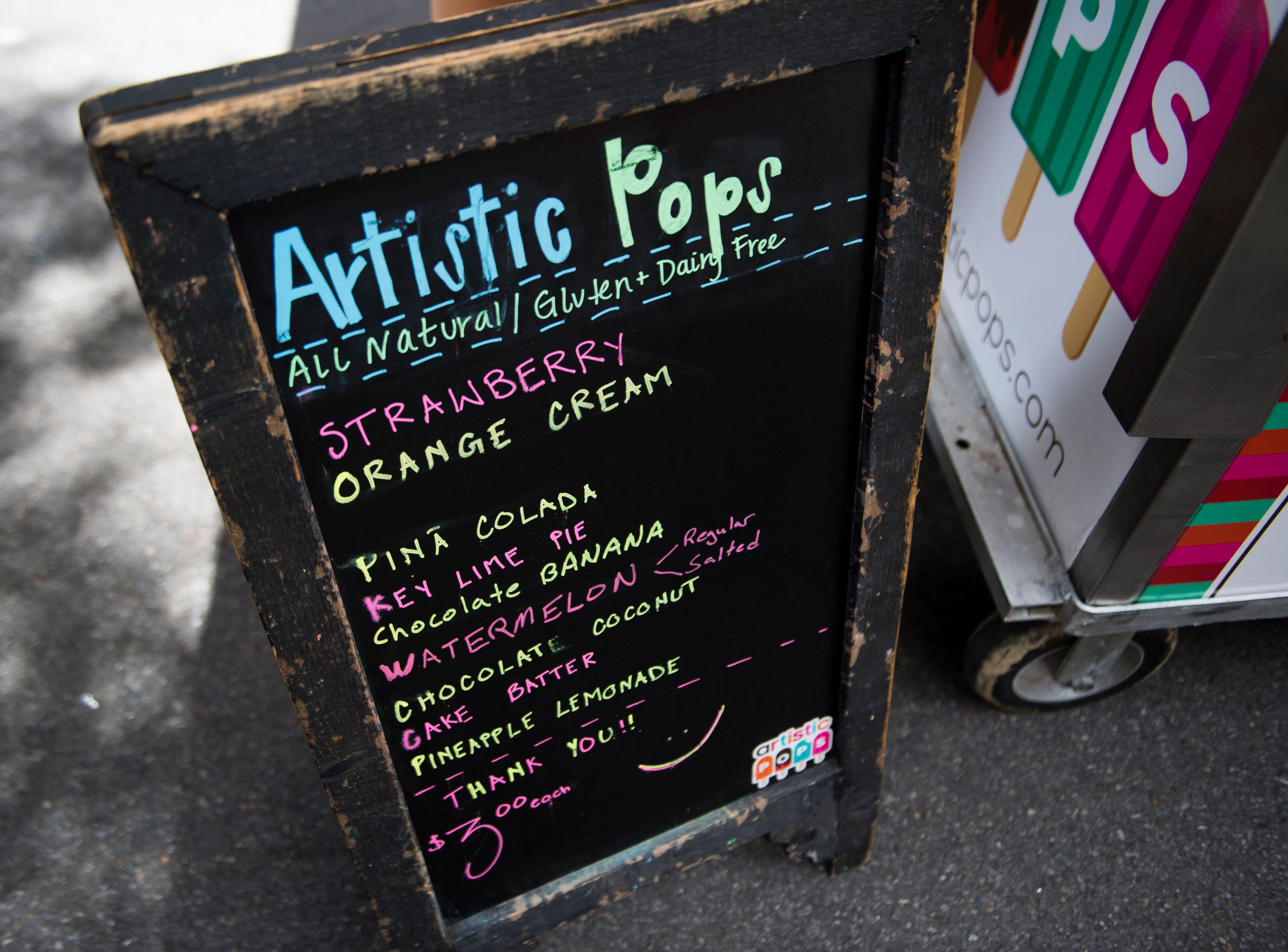 A sign lists the flavors of Artistic Pops at the farmers market in downtown Knoxville Saturday, Aug. 4, 2018. Artistic Pops are gluten free, nut free, and dairy free popsicles.