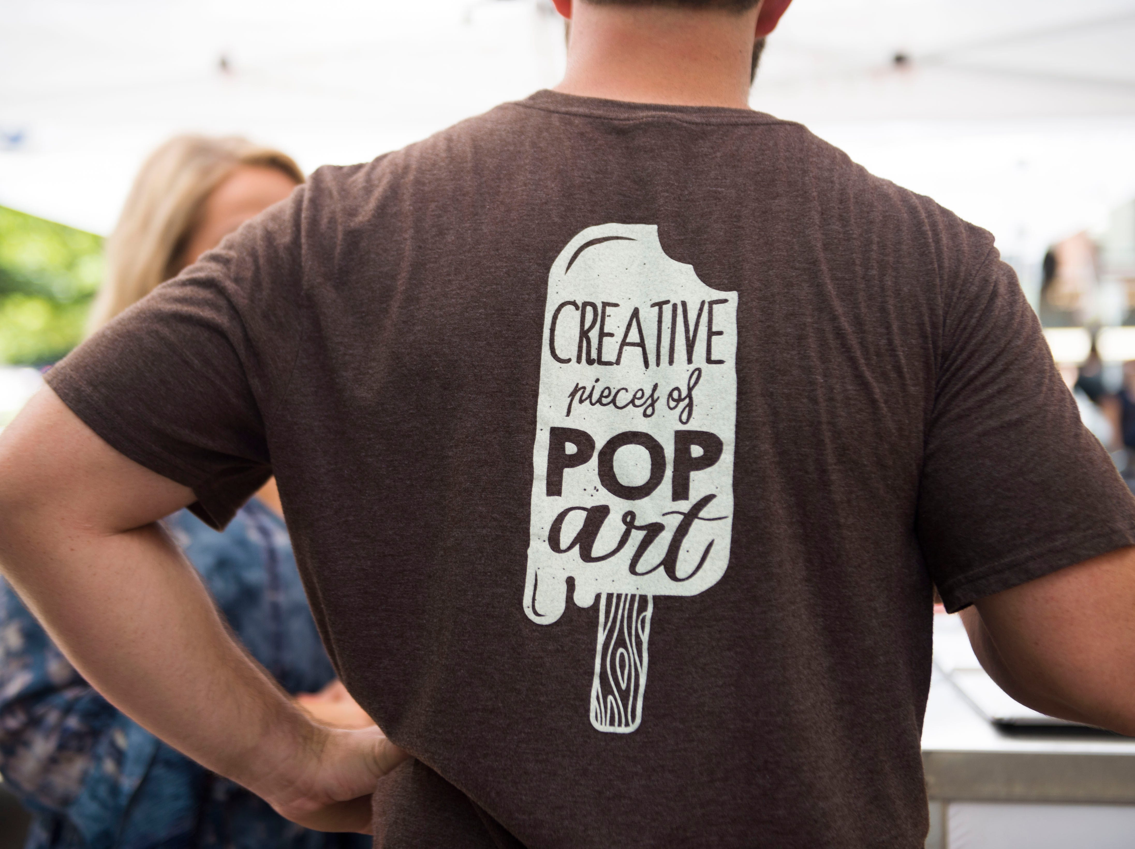 Jon Killebrew, co-owner of Artistic Pops, wears a shirt promoting them, at their stand at the farmers market in downtown Knoxville Saturday, Aug. 4, 2018. Artistic Pops are gluten free, nut free, and dairy free.