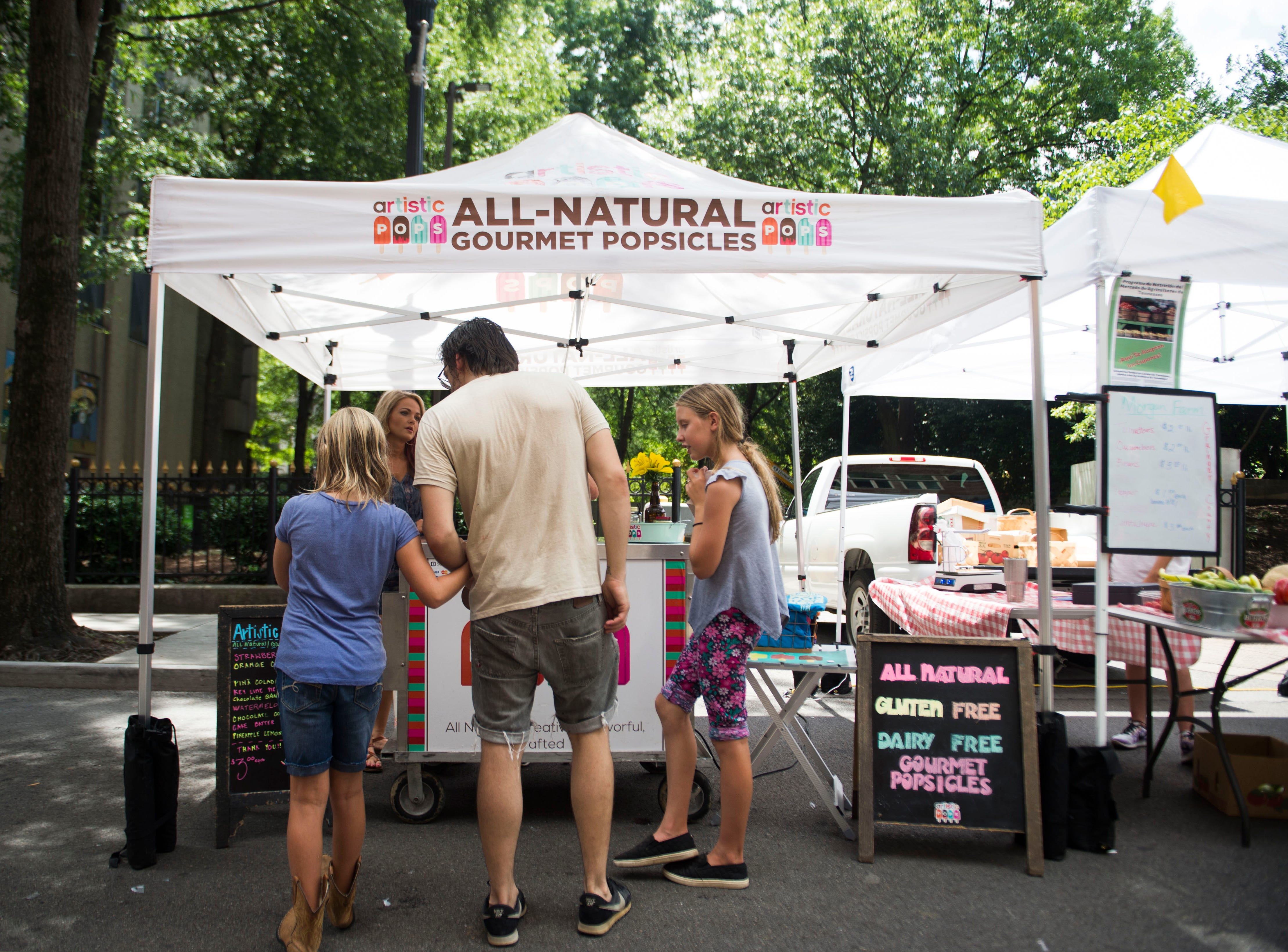 Customers buy Artistic Pops at the farmers market in downtown Knoxville Saturday, Aug. 4, 2018. Artistic Pops are gluten free, nut free, and dairy free popsicles.