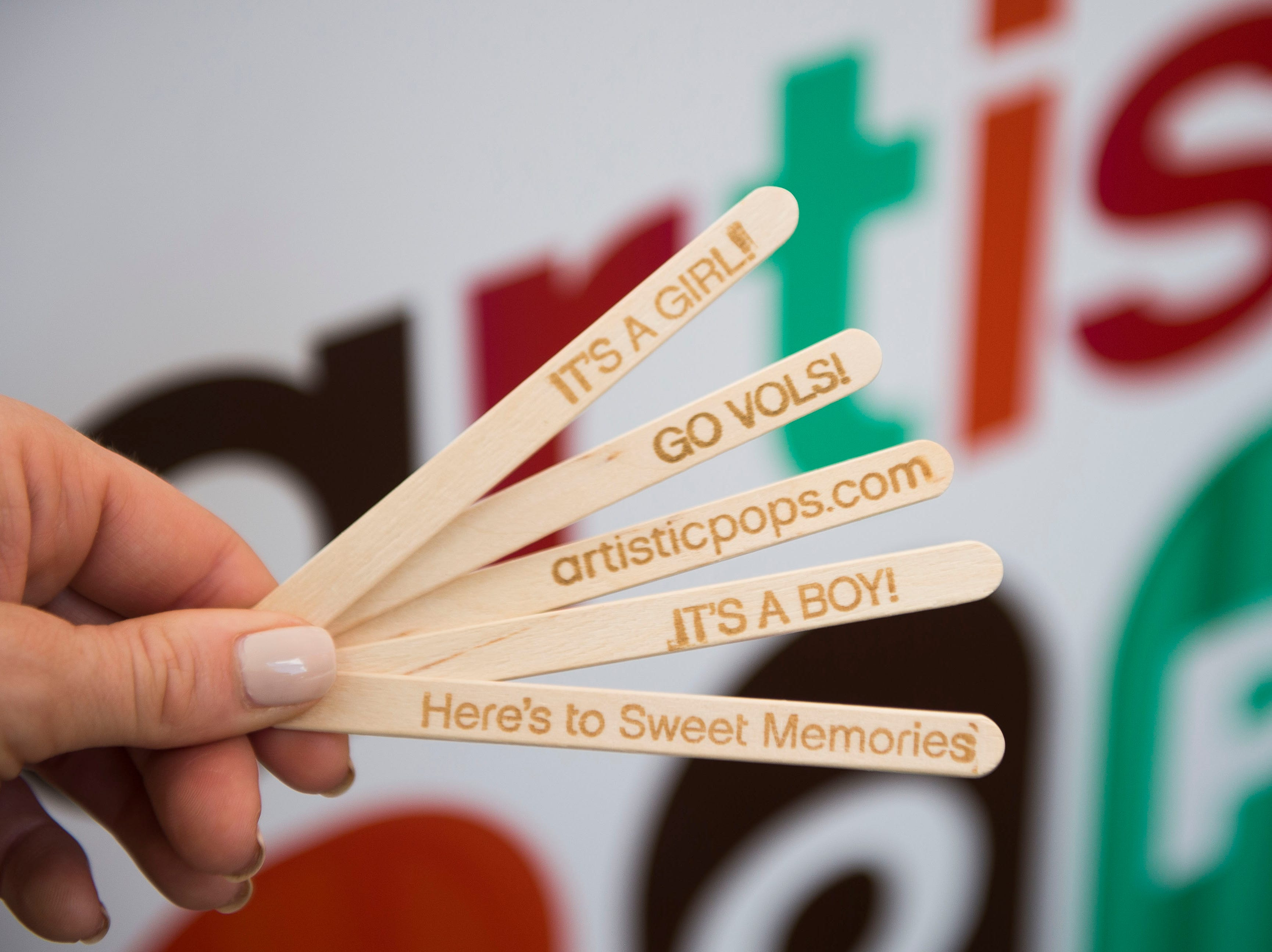 Kristina Killebrew holds custom popsicle sticks at the Artistic Pops stand at the farmers market in downtown Knoxville Saturday, Aug. 4, 2018. Artistic Pops are gluten-free, nut-free, and dairy-free popsicles.