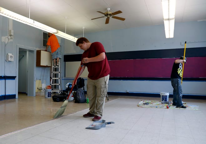 Anthoney Diles, left, Zacahry Holland, center, and Jesse George, right, work to clean and paint a classroom at the former Utica School Saturday, Aug. 4, 2018, on Mount Ida Avenue in Lancaster. People in the Fairfield County Municipal Court community service program have been working to renovate the building from a Head Start school to Lancaster City School's alternative school since the beginning of July.