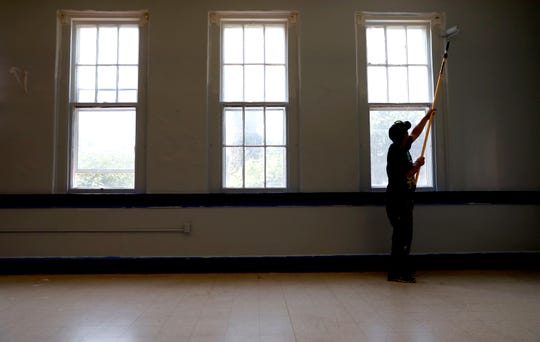 Jesse George paints around windows in a classroom at the old Utica School Saturday, Aug. 4 ,2018, on Mount Ida Avenue in Lancaster. George and other people in the Fairfield County Municipal Court community service program have been renovating the school to get it ready to become Lancaster City School's alternative school.