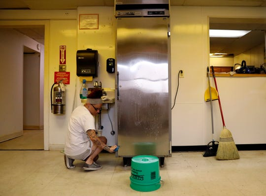 Shannon Lindsey cleans the side of a refrigerator Saturday, Aug. 4, 2018, in the kitchen of the former Utica School in Lancaster. Lindsey and other people in the Fairfield County Municipal Court community service program have been renovating the school to get it ready to become Lancaster City School's alternative school.