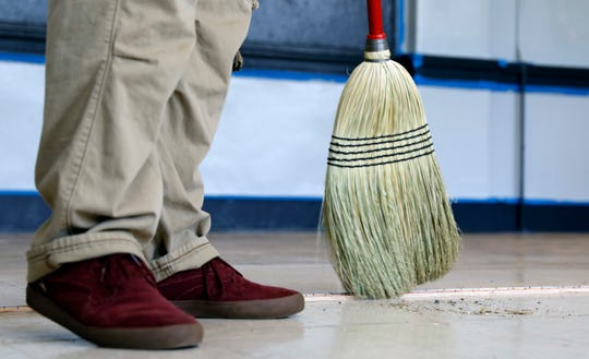 Zachary Holland sweeps the floor of a classroom as he and other people in the Fairfield County Municipal Court community service program transform the former Utica Head Start building on Mount Ida Avenue into an alternative school for Lancaster City Schools.