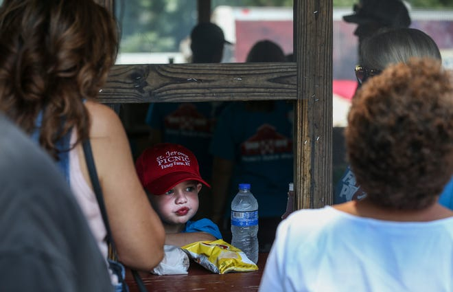A boy looks up at customers while inside the barbecue building at the Fancy Farm picnic Saturday morning.