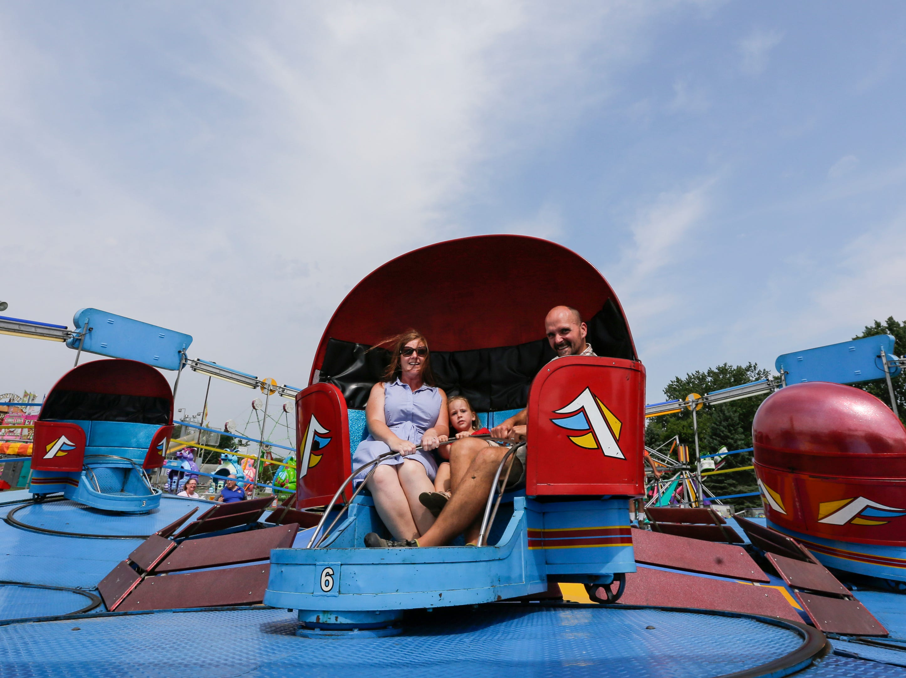 From left, Melissa, Julia, 4, and Andy Jorsch of Oregon ride the tilt-a-whirl during Mishicot Riverfest Saturday, August 4, 2018, in Mishicot, Wis. Josh Clark/USA TODAY NETWORK-Wisconsin