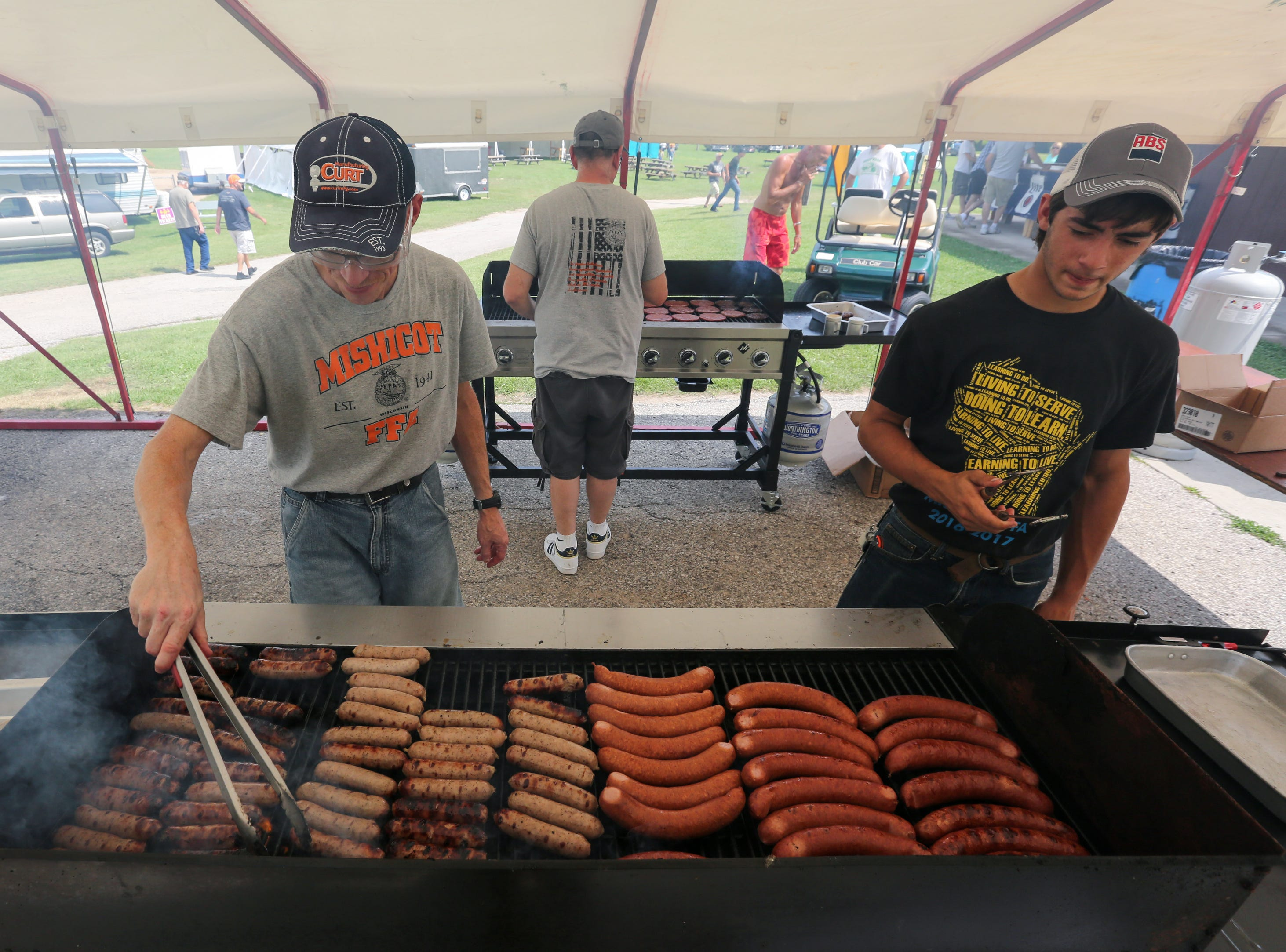 Tom Stinson, left, tends to the brats during Mishicot Riverfest Saturday, August 4, 2018, in Mishicot, Wis. Josh Clark/USA TODAY NETWORK-Wisconsin