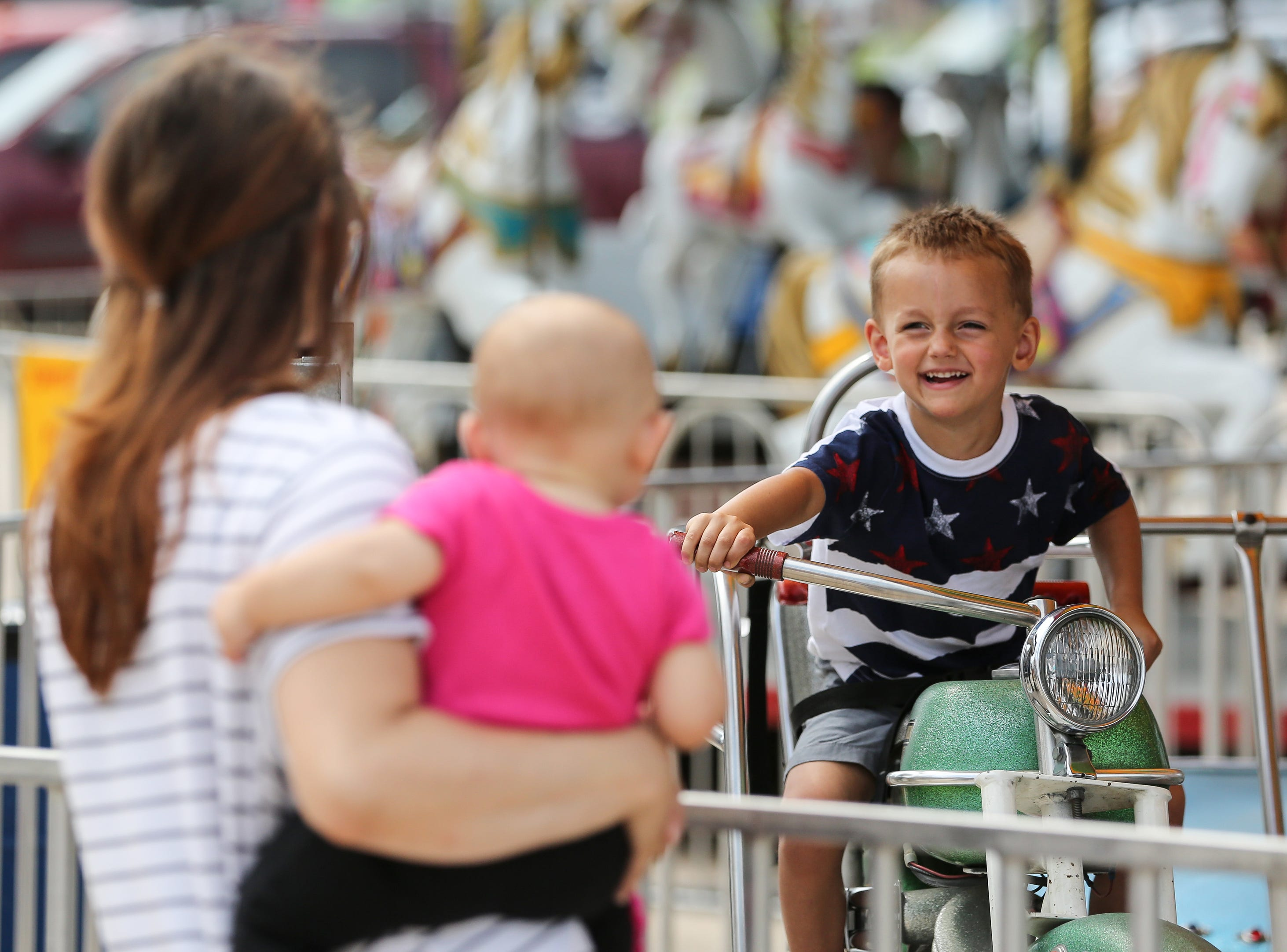 Robert Glaser, 3, smiles on the merry-go-round as he passes his mom and younger sister during Mishicot Riverfest Saturday, August 4, 2018, in Mishicot, Wis. Josh Clark/USA TODAY NETWORK-Wisconsin