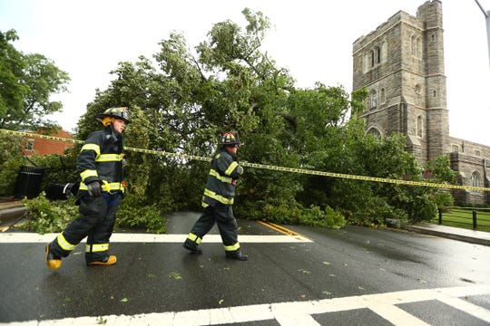 Morristown firefighters pass by a fallen treen on South Street. Morristown teen, Kyle Gehsmann escaped through his damaged driver side door shaken but uninjured after a violent afternoon storm uprooted a large tree in front of St Peters Episcopal Church onto the roof of his car.  August 3, 2018. Morristown, NJ