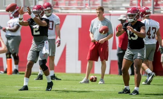 Quearterbacks Jalen Hurts (2) and Tua Tagovailoa (13) take snaps side by side as the University of Alabama football team holds practice in Bryant-Denny Stadium on the Alabama campus in Tuscaloosa, Ala. on Saturday August 4, 2018.