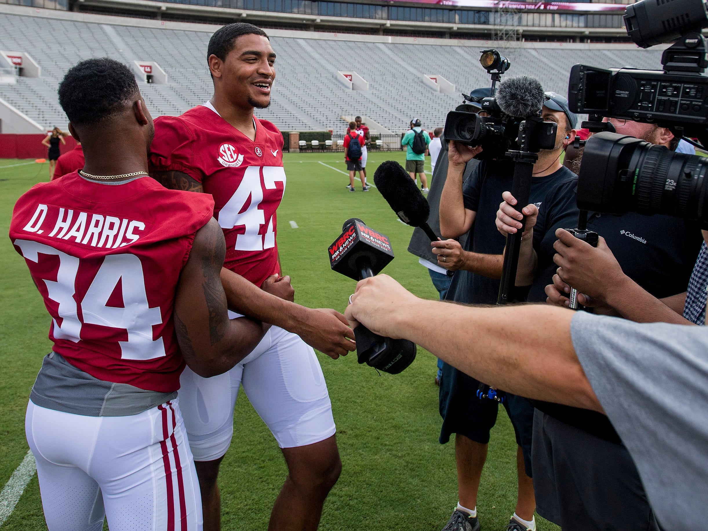 University of Alabama's Damien Harris (34) and Christian Miller (47)joke around with the media before fan day on the Alabama campus in Tuscaloosa, Ala. on Saturday August 4, 2018.