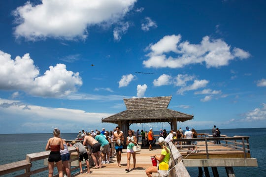 """A plane displaying a PETA banner that reads """"Keep Hookers off the Pier - Ban Fishing!"""" flies over the Naples Pier on Saturday, Aug. 4, 2018."""