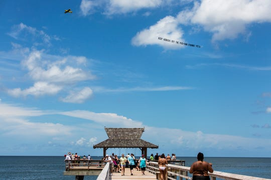 "A plane displaying a PETA banner that reads ""Keep Hookers off the Pier - Ban Fishing!"" flies over the Naples pier on Saturday."