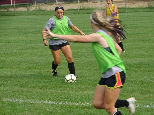 Watkins Memorial sophomore Sommer Branham looks to make a pass ahead to freshman Taylor Evec this past Friday during an intrasquad scrimmage.
