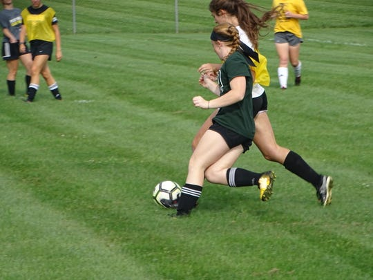 Watkins Memorial junior Emily Irwin attempts to break past sophomore Ruth Merz this past Friday during an intrasquad scrimmage.