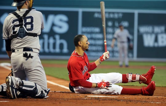 Boston Red Sox's Mookie Betts sits on the dirt in front of New York Yankees catcher Austin Romine after a close pitch by Yankees starter Luis Severino during the first inning of a baseball game at Fenway Park, Friday, Aug. 3, 2018, in Boston.