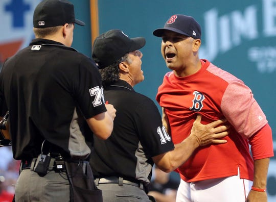 Boston Red Sox manager Alex Cora is held back by first base umpire Phil Cuzzi (10) as Cora argues with home plate umpire Adam Hamari after both Red Sox and New York Yankees pitchers were warned against hitting batters, during the first inning of a baseball game at Fenway Park, Friday, Aug. 3, 2018, in Boston. Cora was ejected.
