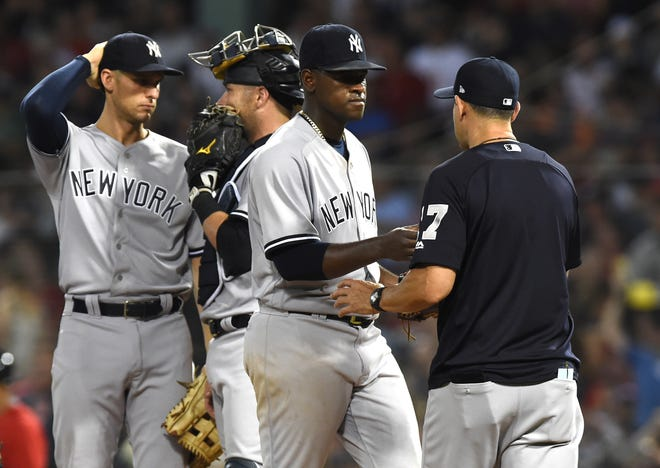 Aug 3, 2018; Boston, MA, USA; New York Yankees starting pitcher Luis Severino (40) hands the ball to manager Aaron Boone (17) during the sixth inning against the Boston Red Sox at Fenway Park.