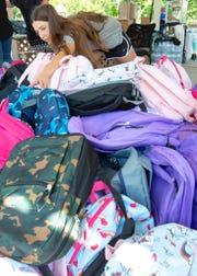 Anna Ortiz, 13, of Las Cruces, reaches for a backpack to give away during FYI's second annual back-to-school event at Pioneer Park. Ortiz donated 135 backpacks towards the event.