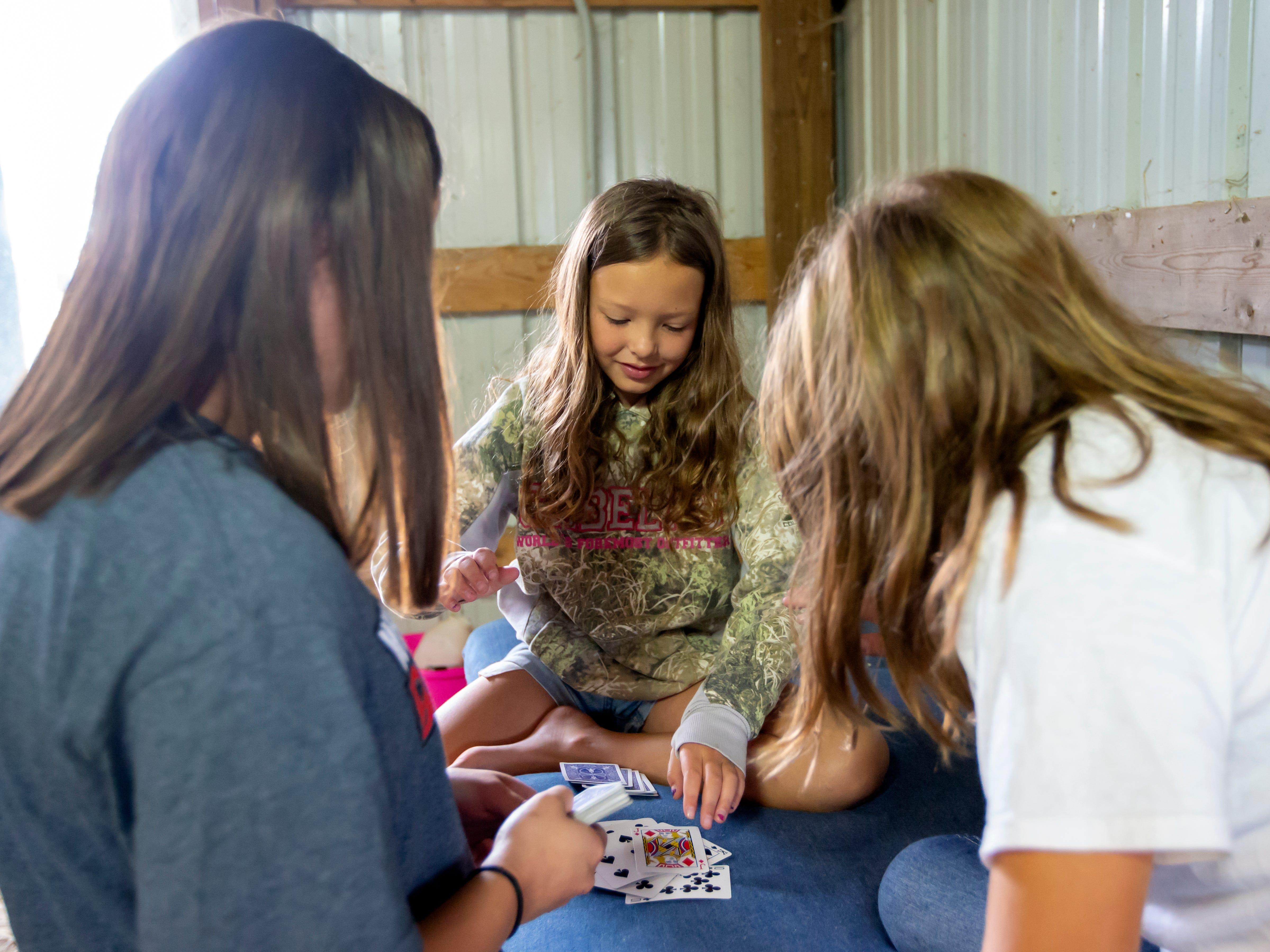Scarlett Poppy from Omro plays a card game in the barn at the fairgrounds with friends during the Winnebago County Fair on Friday, Aug. 3, 2018.