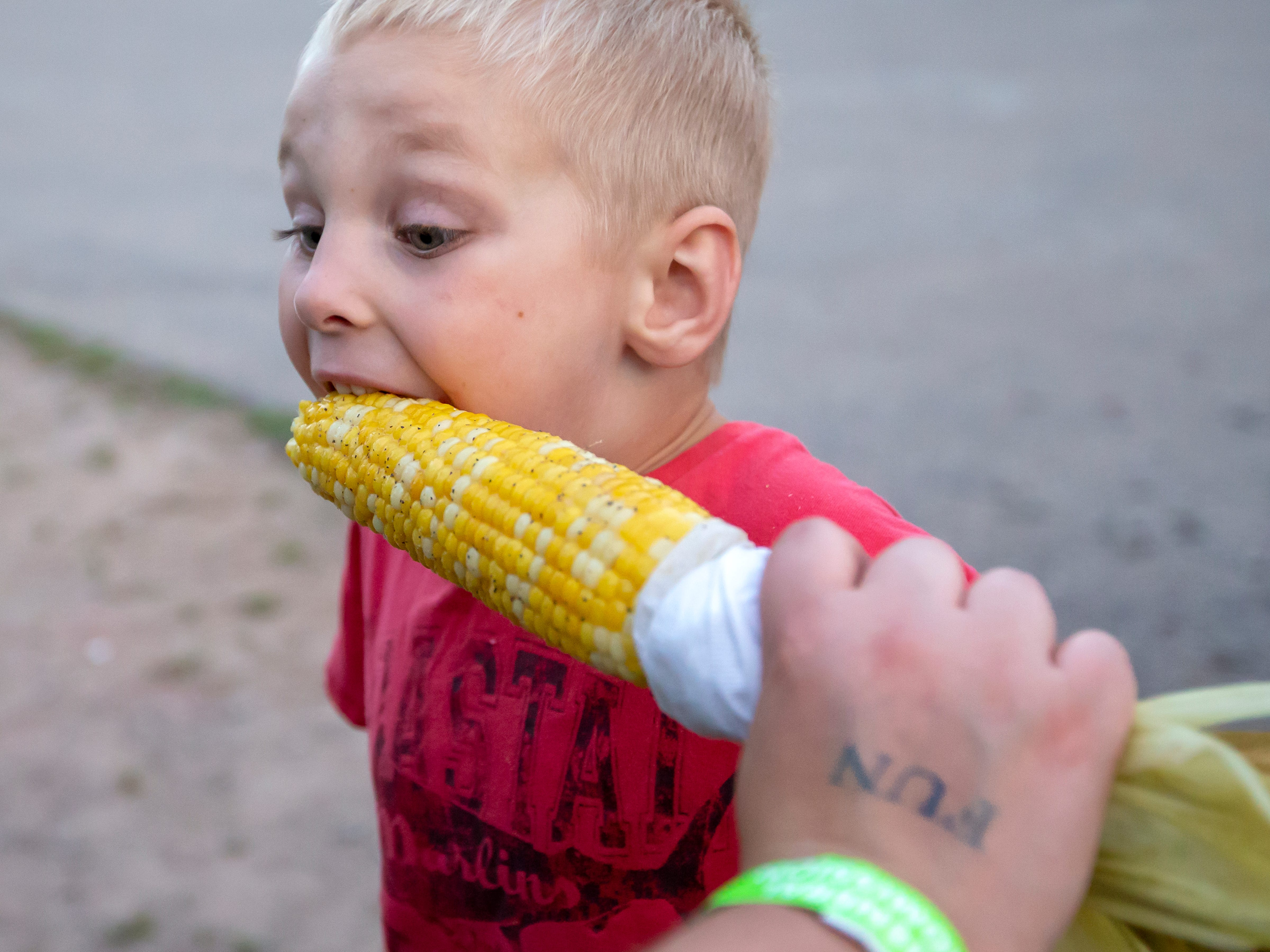 Maverick Bartow of Oshkosh takes a bite into corn on the cob during the Winnebago County Fair on Friday, Aug. 3, 2018.