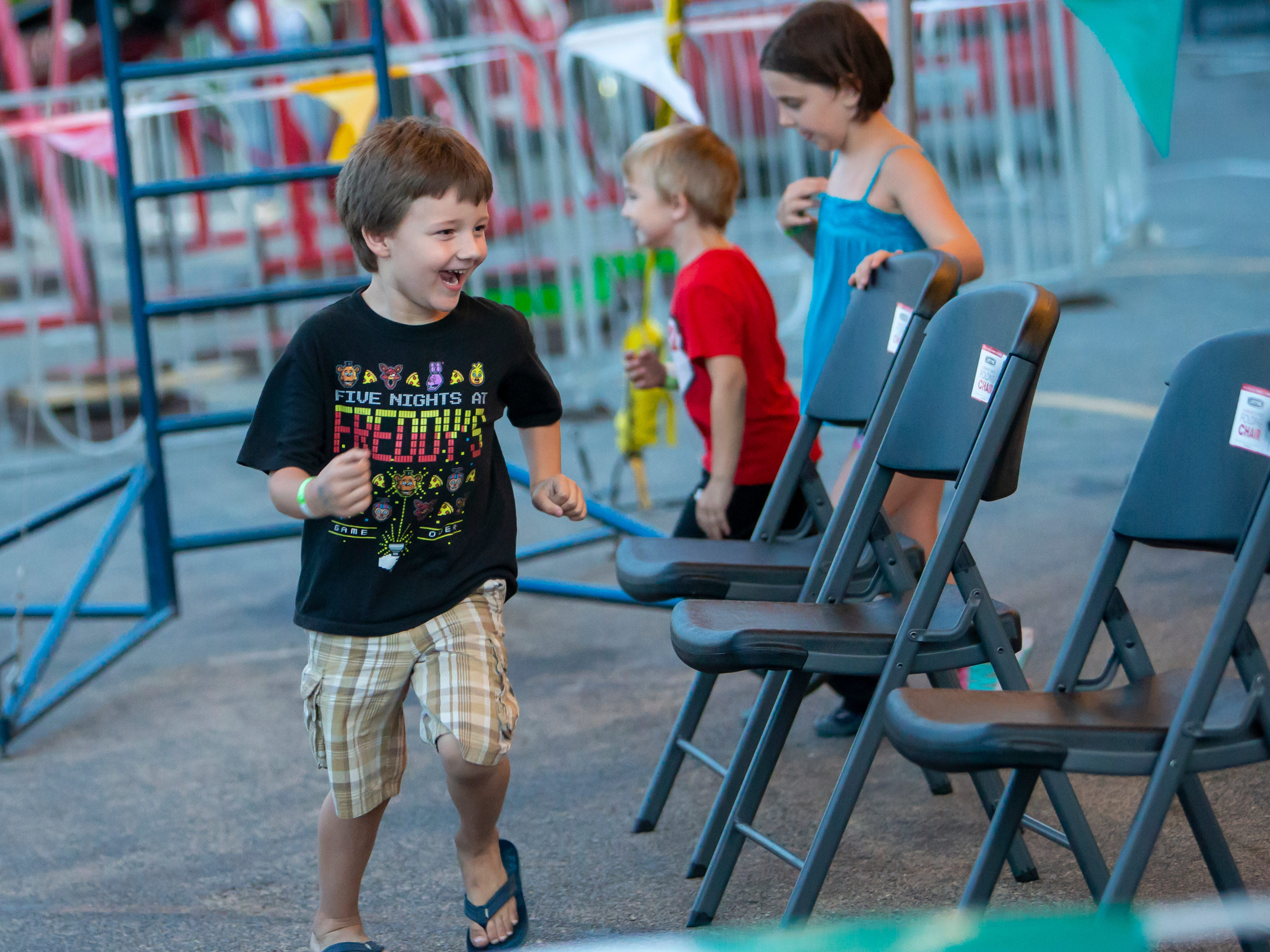 Children races around chairs playing musical chairs at the Mr. Ed's Magical Circus Show event during the Winnebago County Fair on Friday, Aug. 3, 2018.
