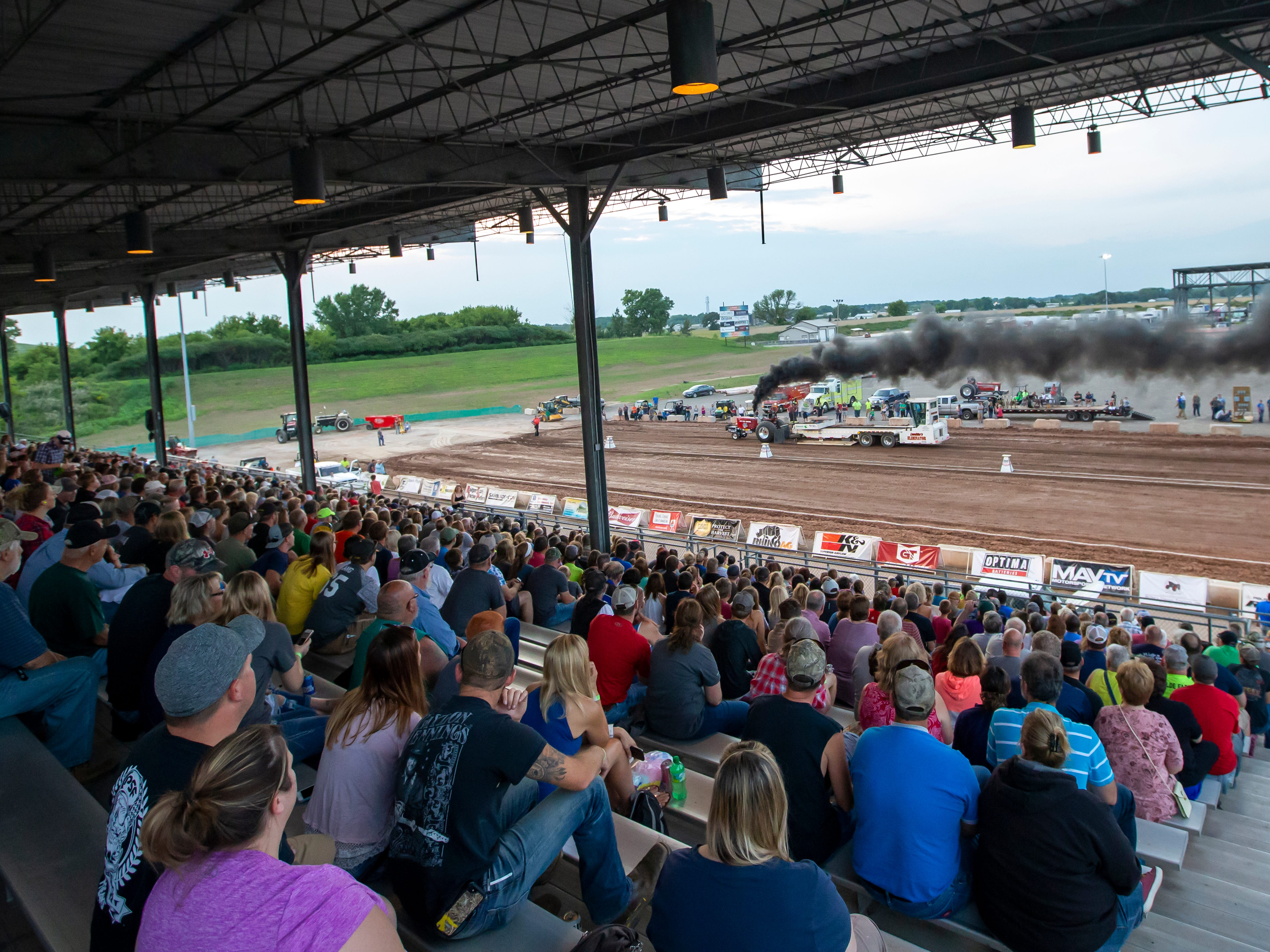 Spectators watch the Badger State Truck & Tractor Pull during the Winnebago County Fair on Friday, Aug. 3, 2018.