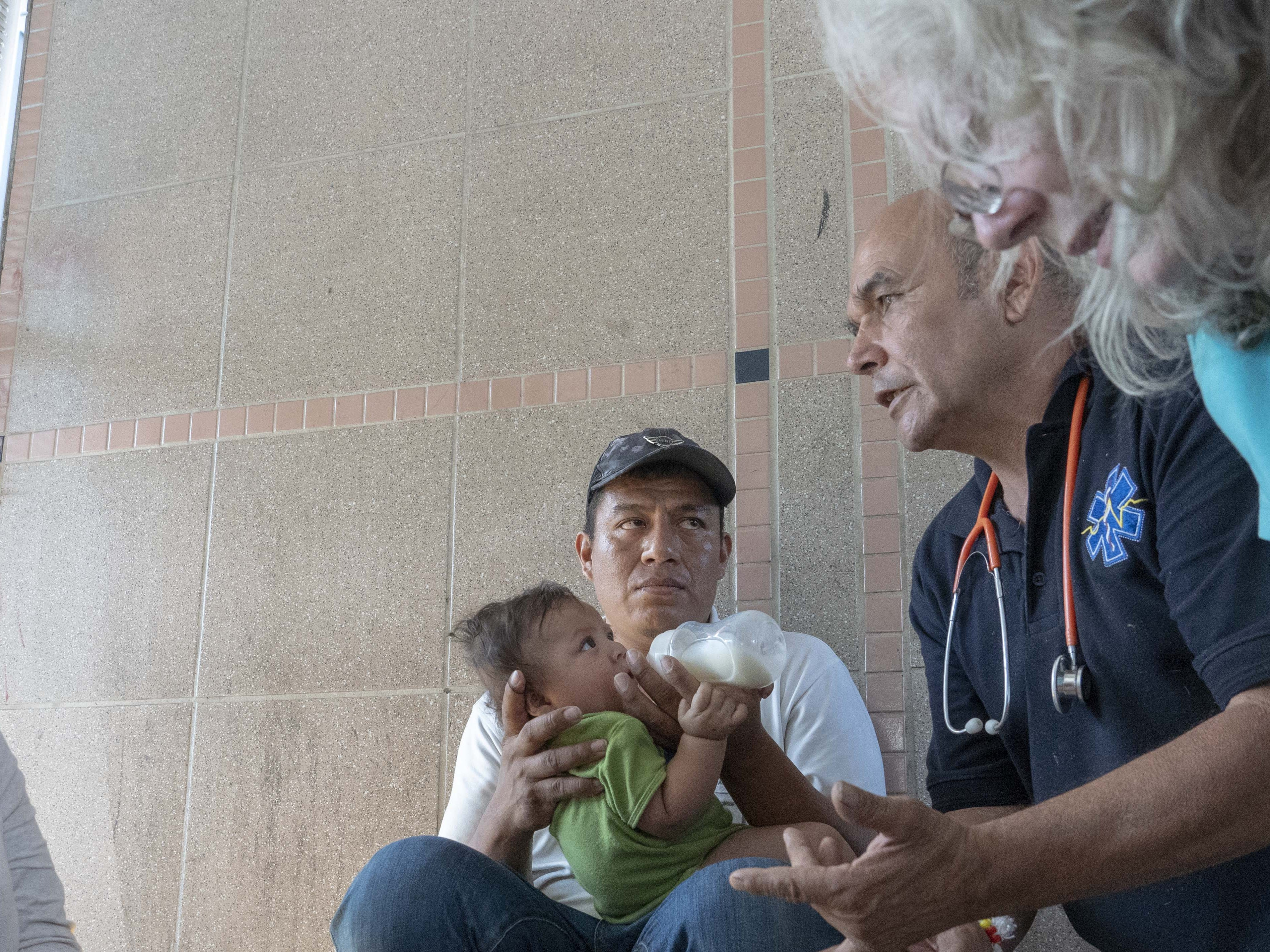 Elation Laguna Flores, Miriam Chino Gonzalez, and their baby, Ivan Laguna, get help from Frank Martin and Janice Pulliam at the DeConcini port of entry. The family from Guerrero, Mexico, were the only ones waiting in line to seek asylum at the border crossing at the time.