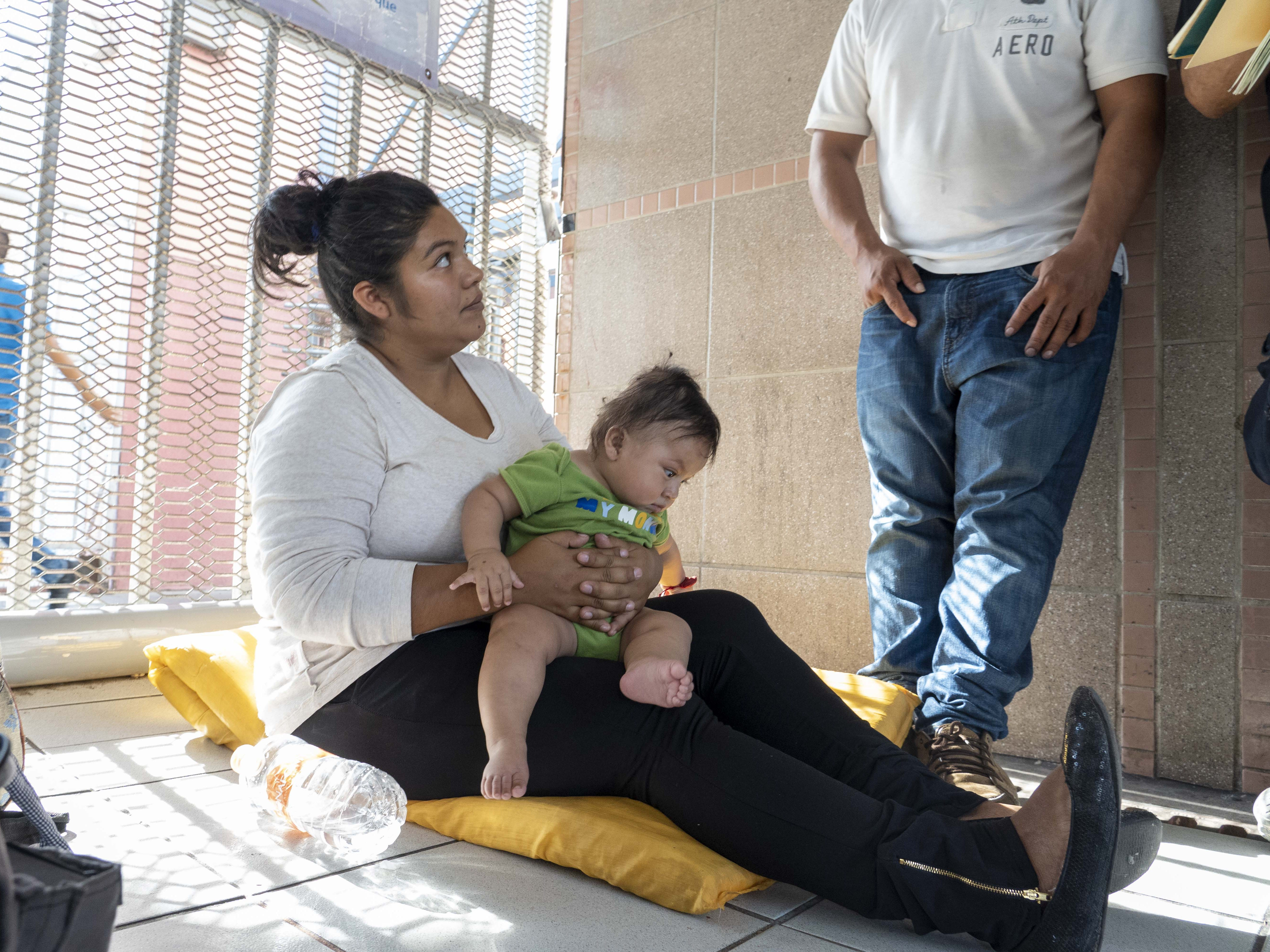 Elation Laguna Flores, Miriam Chino Gonzalez, and their baby, Ivan Laguna,  wait at the DeConcini port of entry. The family from Guerrero, Mexico, were the only ones waiting in line to seek asylum at the border crossing at the time. Customs officers increased the processing of asylum seekers in Nogales, clearing the lengthy queue in a matter of days.