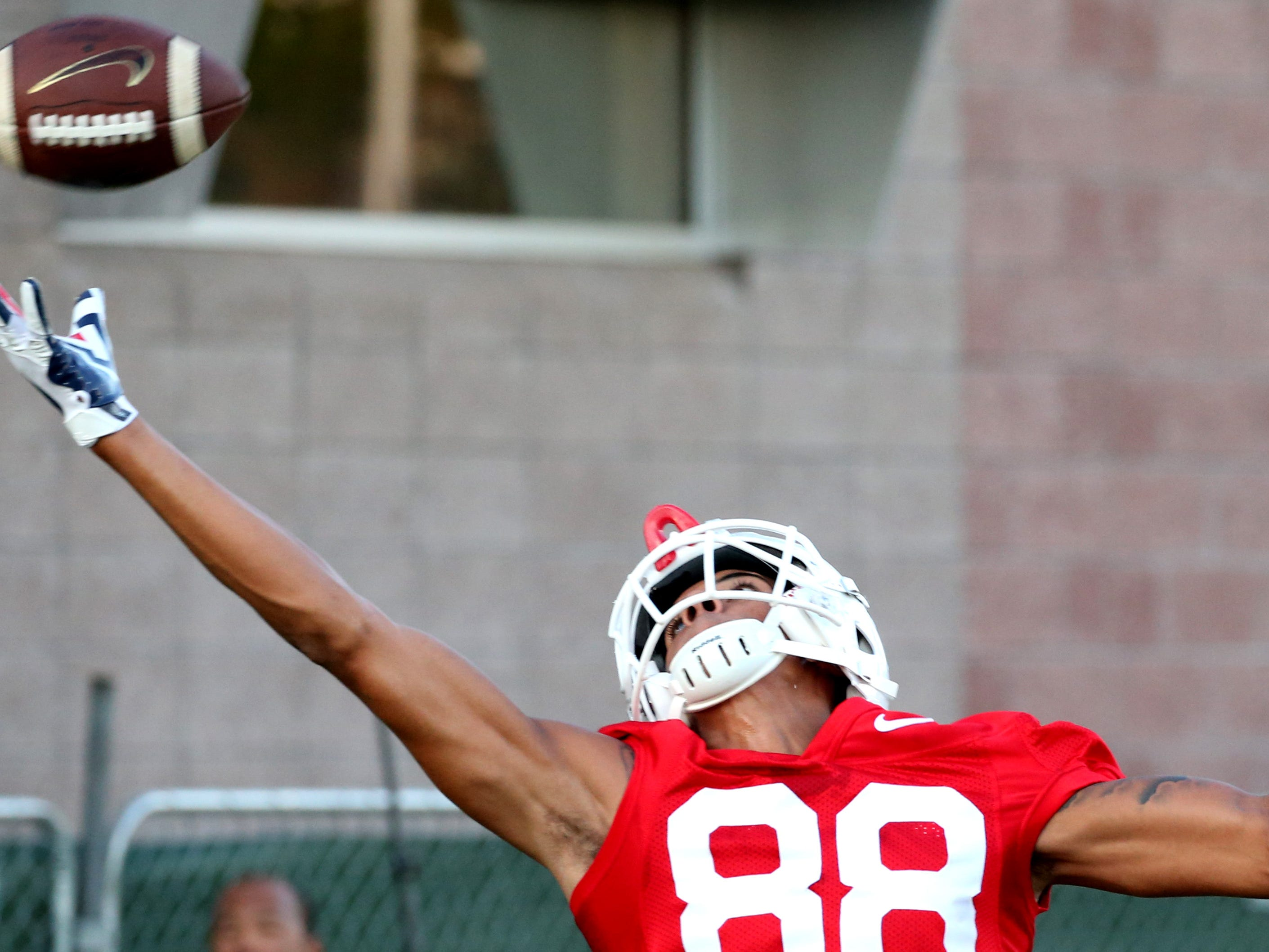Receiver Tre Adams stretches but can't get to a high throw as he runs route drills at the first day of practice for the University of Arizona, Friday, August 3, 2018, Tucson, Ariz.