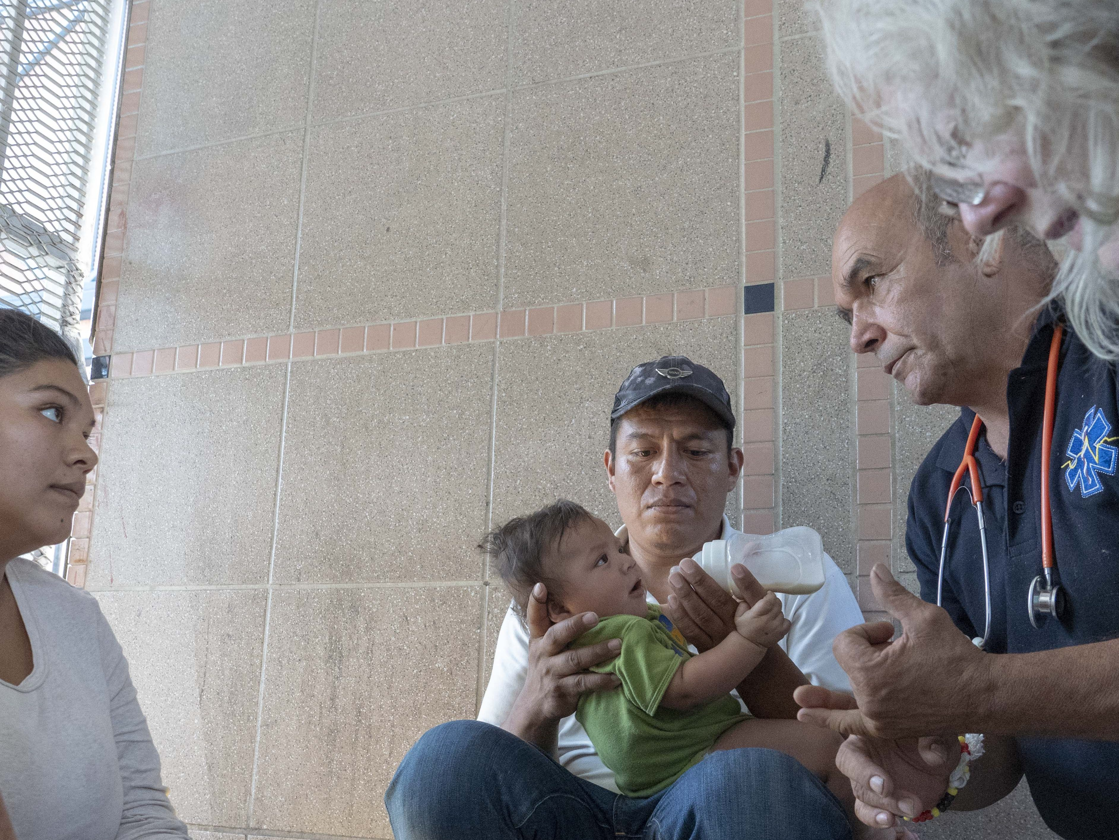 Elation Laguna Flores, Miriam Chino Gonzalez, and their baby, Ivan Laguna, get help from Frank Martin and Janice Pulliam at the DeConcini port of entry. Customs officers increased the processing of asylum seekers in Nogales, clearing the lengthy queue of asylum seekers in a matter of days.