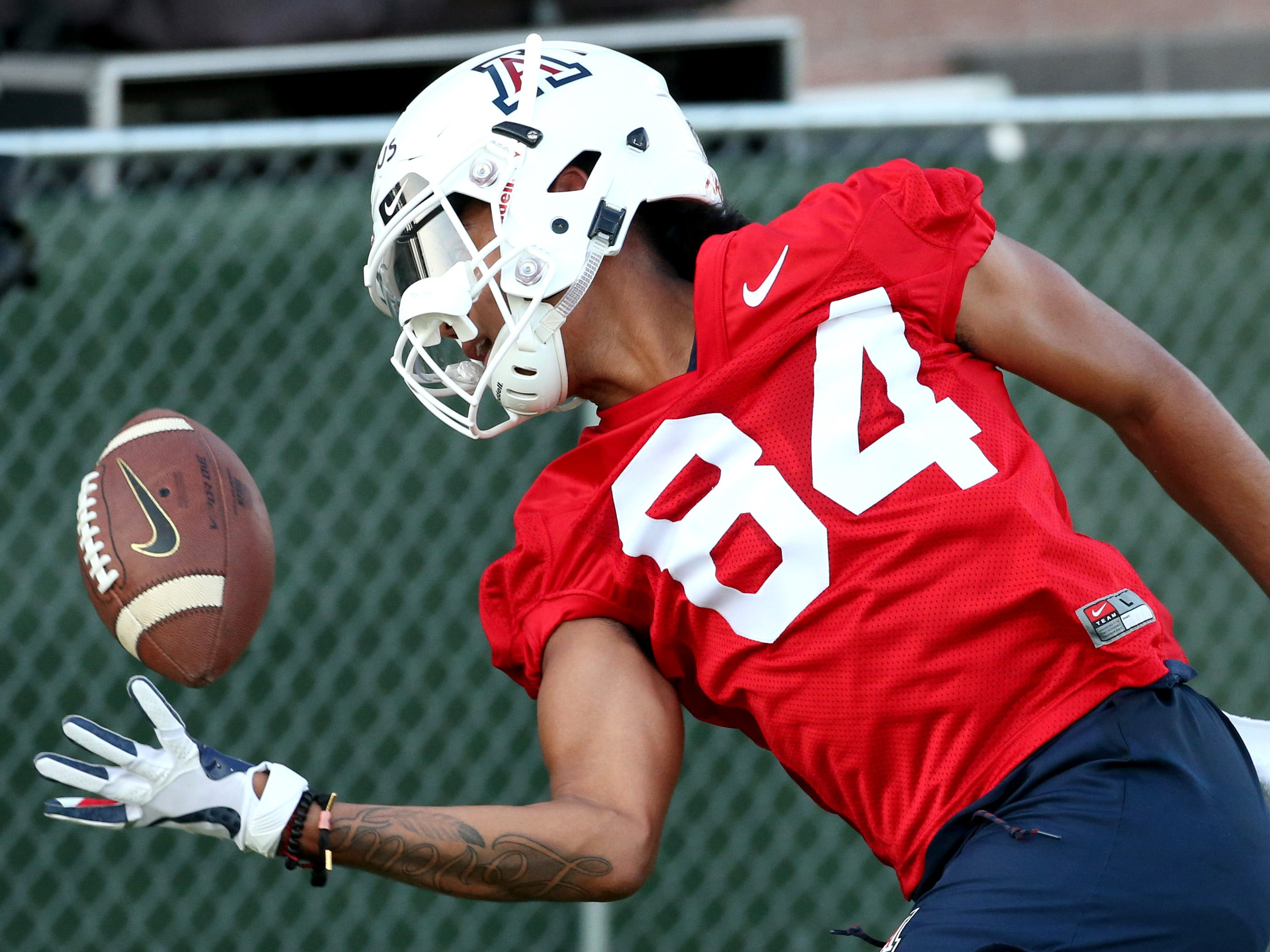Wide receiver Thomas Marcus juggles the ball while trying to haul in a catch running route drills at the first day of practice for the University of Arizona, Friday, August 3, 2018, Tucson, Ariz.