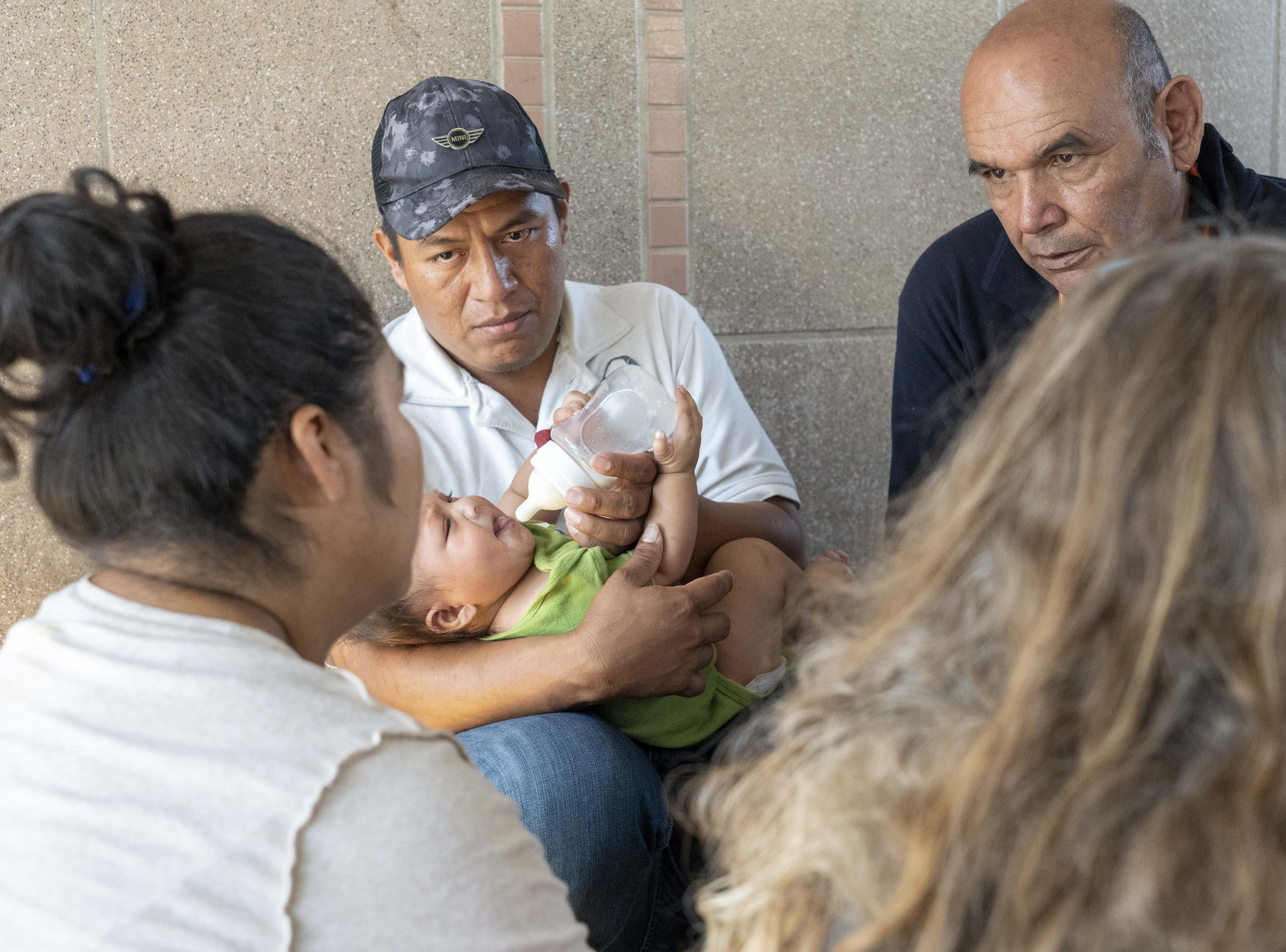Elation Laguna Flores, Miriam Chino Gonzalez, and their baby, Ivan Laguna,  get help from Frank Martin, a Mexican Samaritan, at the DeConcini port of entry. Customs officers increased the processing of asylum seekers in Nogales, clearing the lengthy queue in a matter of days.