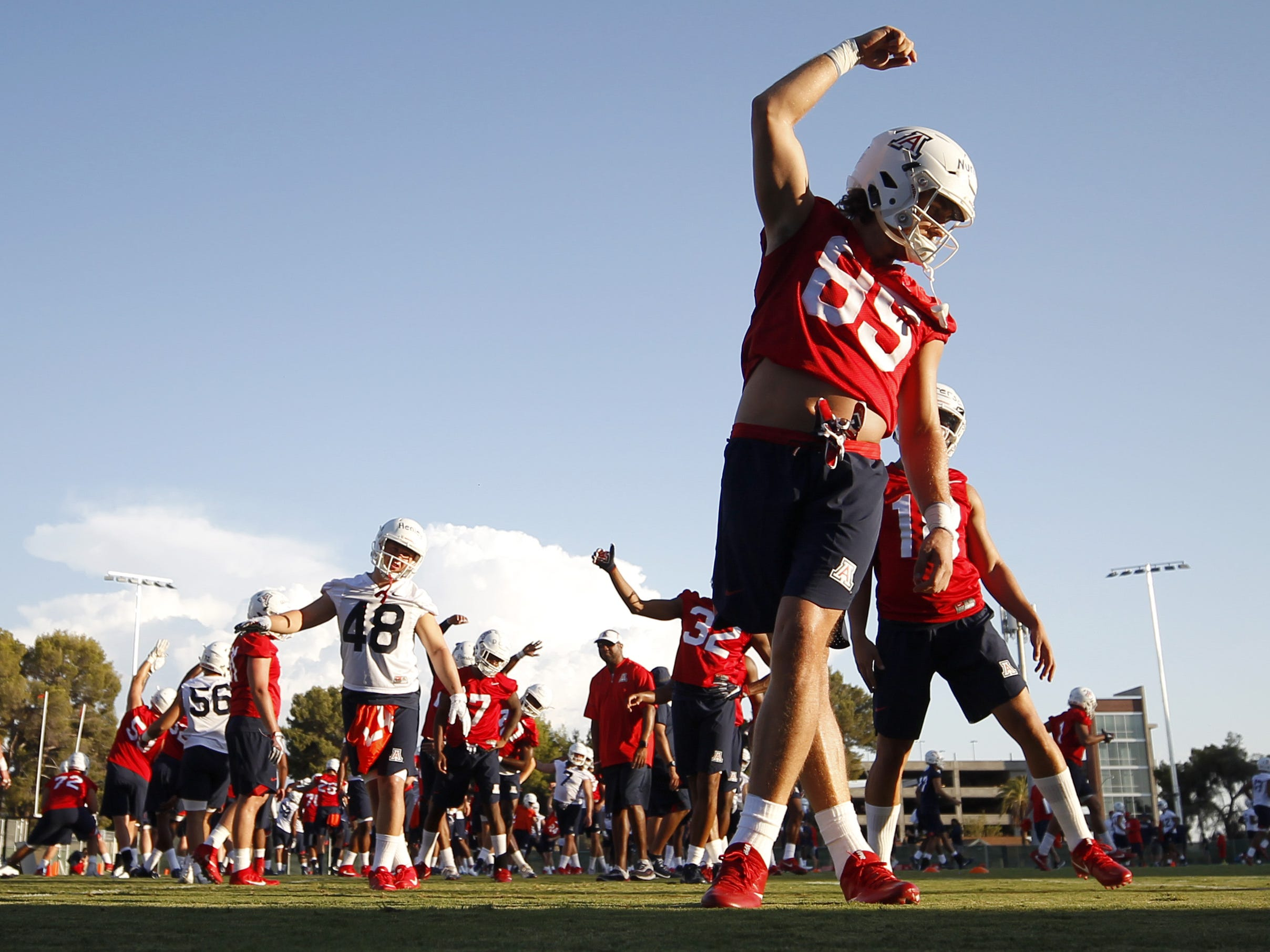 The Wildcats get limbered up as the team gets ready for  the first day of practice for the University of Arizona, Friday, August 3, 2018, Tucson, Ariz.
