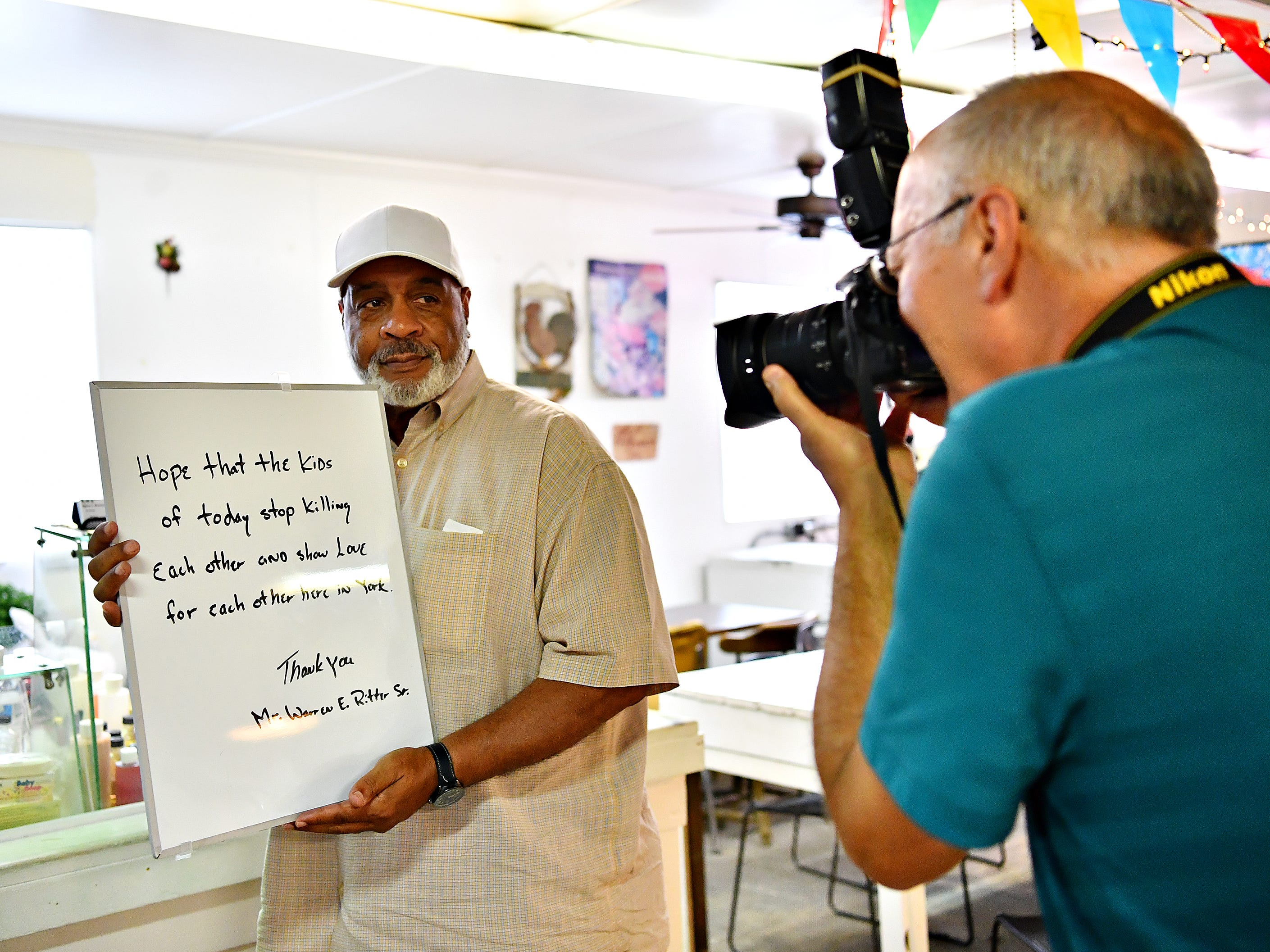 "Warren Ritter Sr., left, of West Manchester Township, is photographed by York Storyman Randy Flaum, as messages of hope are collected for Author Anne Clark's, book of hope,""Messages of Hope from York!"" at Penn Market in York City, Saturday, Aug. 4, 2018.  Clark, the director of community outreach for Lincoln Charter School, says that after writing her own book, ""The Journey of Hope,"" she came to realize that the community of York needed its own book. Dawn J. Sagert"
