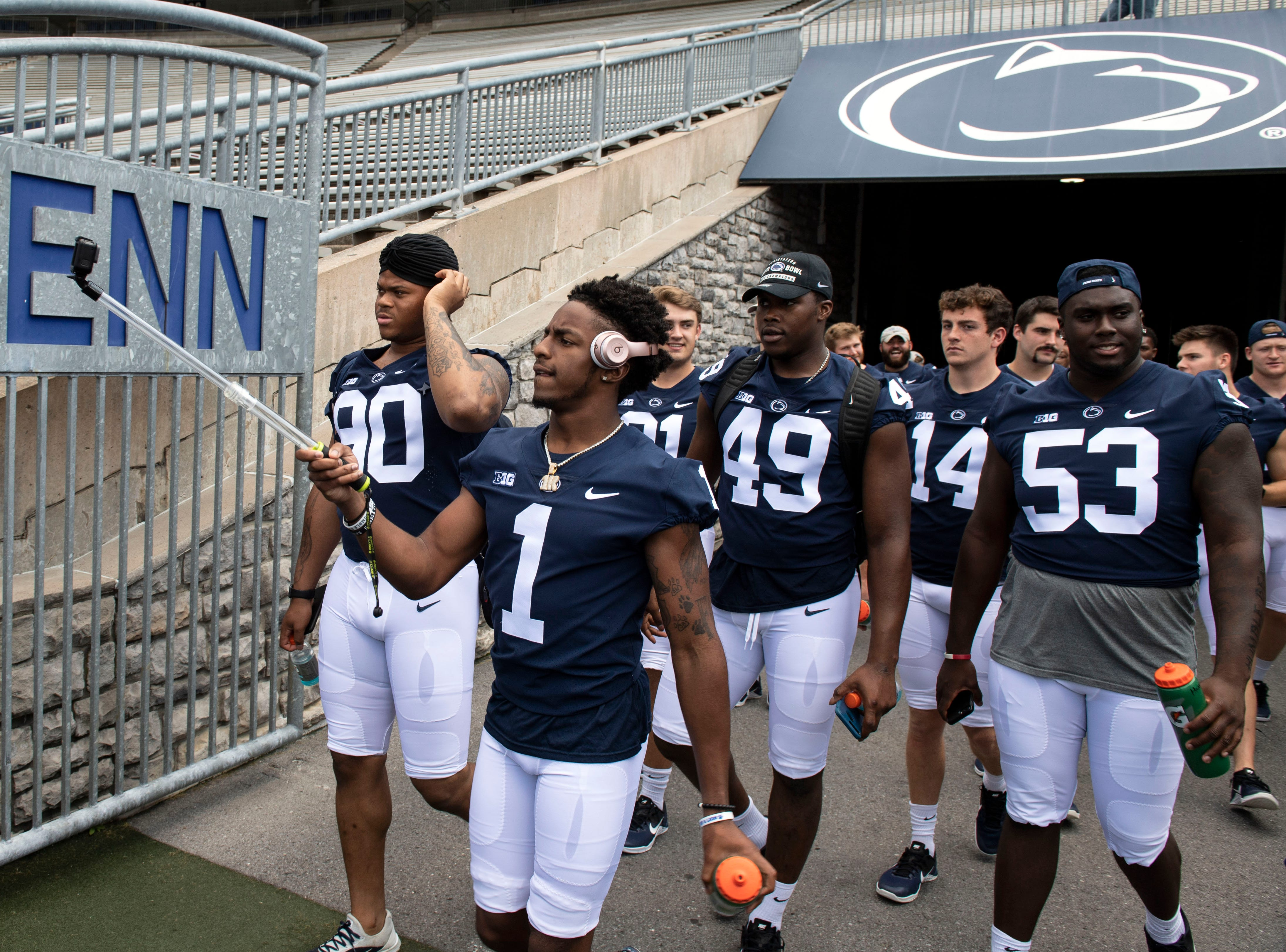 K.J. Hamler (1) records on a GoPro as the Penn State football team makes its way on the field during media day at Beaver Stadium on Saturday, August 4, 2018.