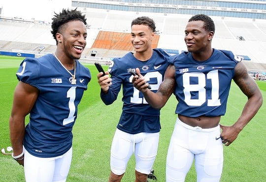 Mac Hippenhammer (12) and Cam Sullivan-Brown (81) joke around while KJ Hamler (1) speaks with reporters during media day at Beaver Stadium on Saturday, August 4, 2018.