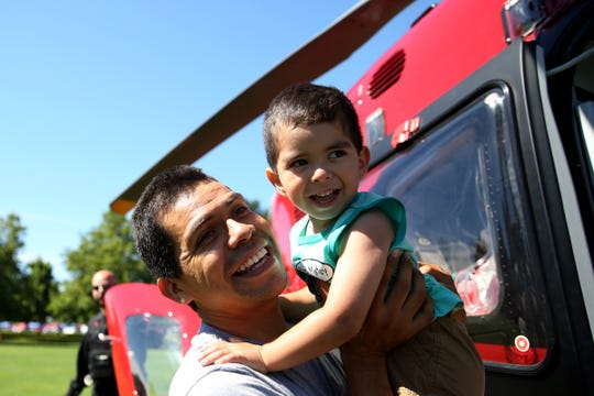Arturo Barrera-Montoya, 35, of Salem, carries his son, Arturo Barrera, 2, past a medical emergency helicopter on display during Riverfront Family Fest at Riverfront Park in Salem on Saturday, Aug. 4, 2018.